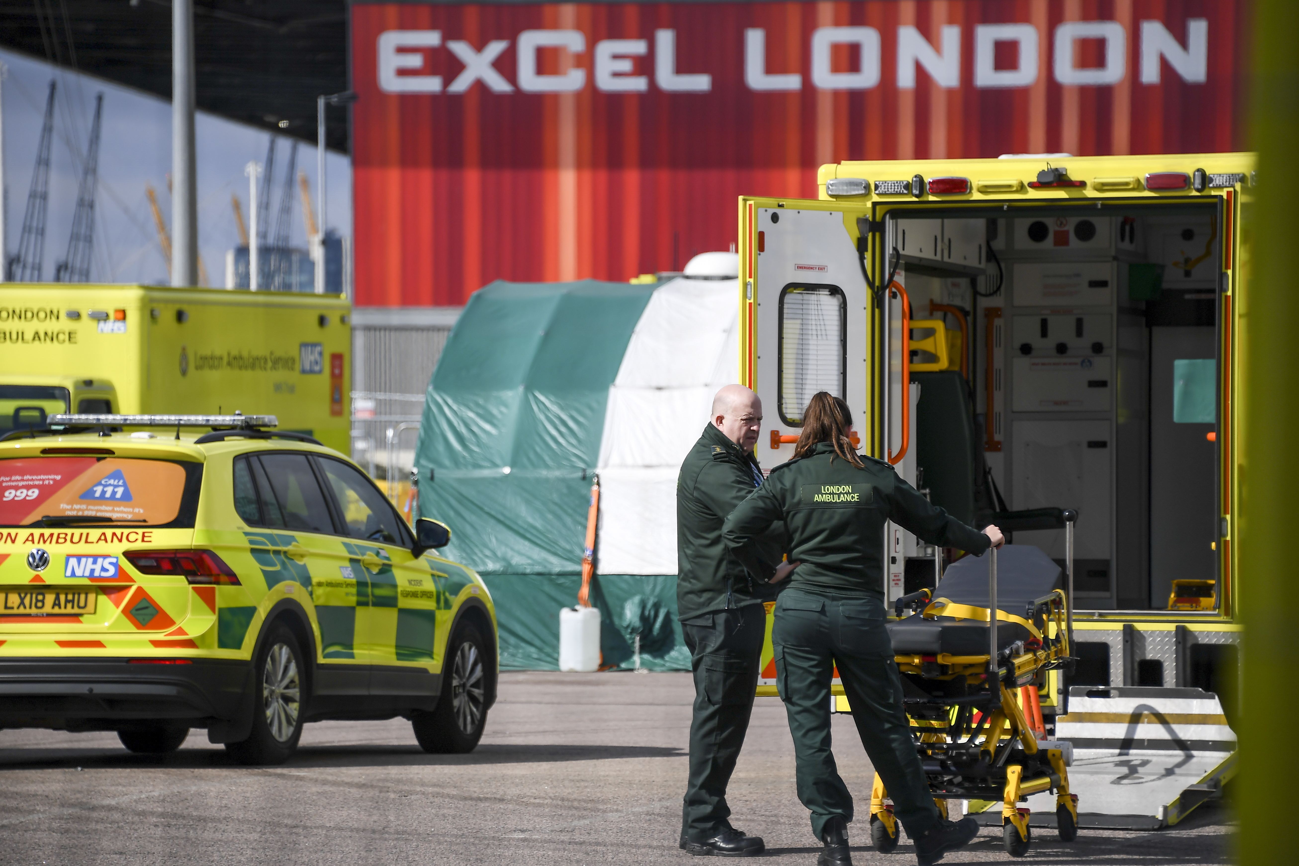 Ambulance staff at the ExCel Center in London, Thursday, April 2, 2020, that is being turned into a 4000 bed temporary hospital know as NHS Nightingale to help deal with some of the coronavirus outbreak victims in London. The new coronavirus causes mild or moderate symptoms for most people, but for some, especially older adults and people with existing health problems, it can cause more severe illness or death. (AP Photo/Alberto Pezzali)
