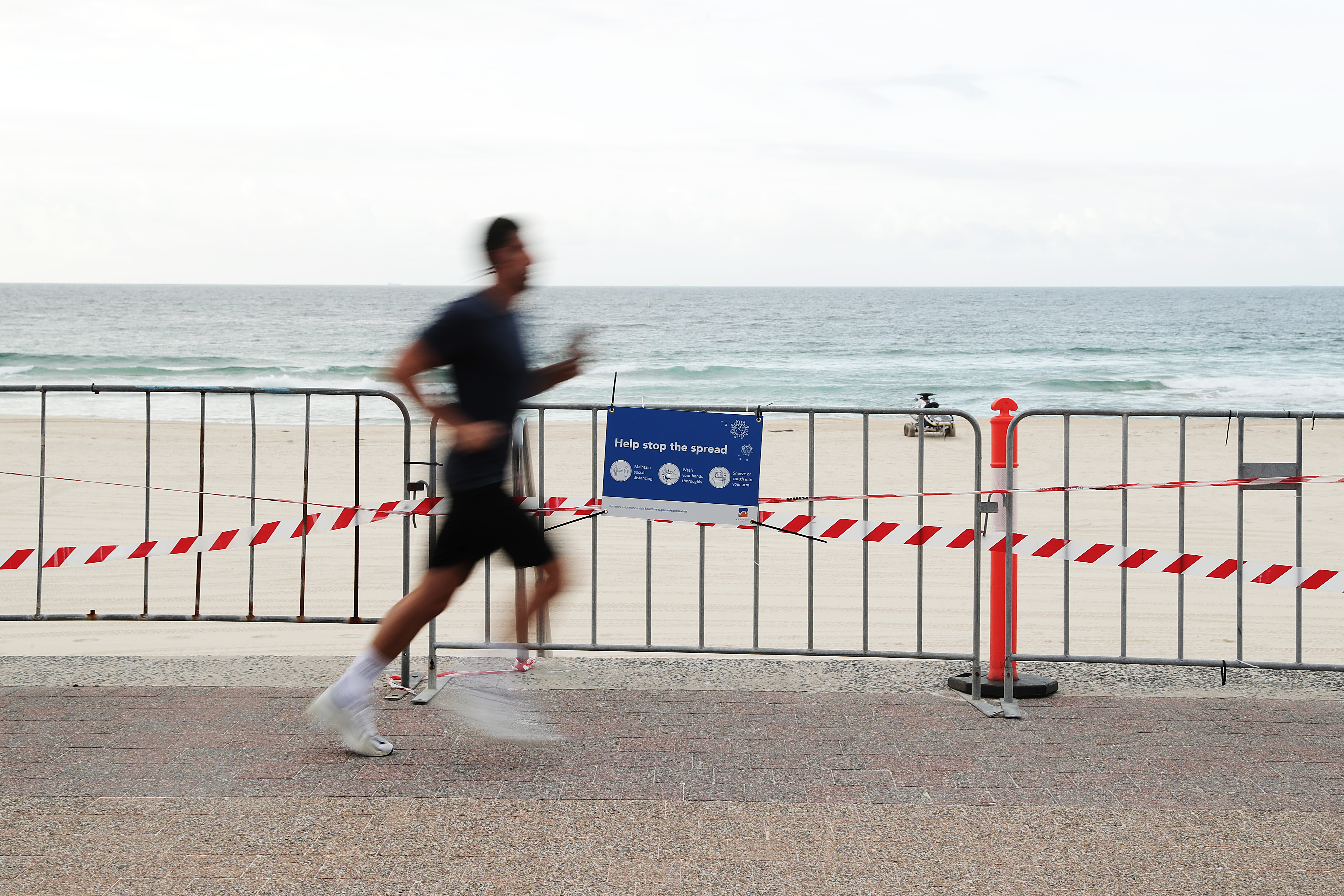 SYDNEY, AUSTRALIA - APRIL 01: A jogger runs along Bondi Beach on April 01, 2020 in Sydney, Australia. The Australian government has introduced further restrictions on movement and gatherings in response to the ongoing COVID-19 pandemic. Public gatherings are now limited to two people, while Australians are being urged to stay home unless absolutely necessary. New South Wales and Victoria have also enacted additional measures to allow police the power to fine people who breach the two-person outdoor gathering limit or leave their homes without a reasonable excuse. Queensland, Western Australia, South Australia, Tasmania and the Northern Territory have all closed their borders to non-essential travellers and international arrivals into Australia are being sent to mandatory quarantine in hotels for 14 days. (Photo by Mark Metcalfe/Getty Images)