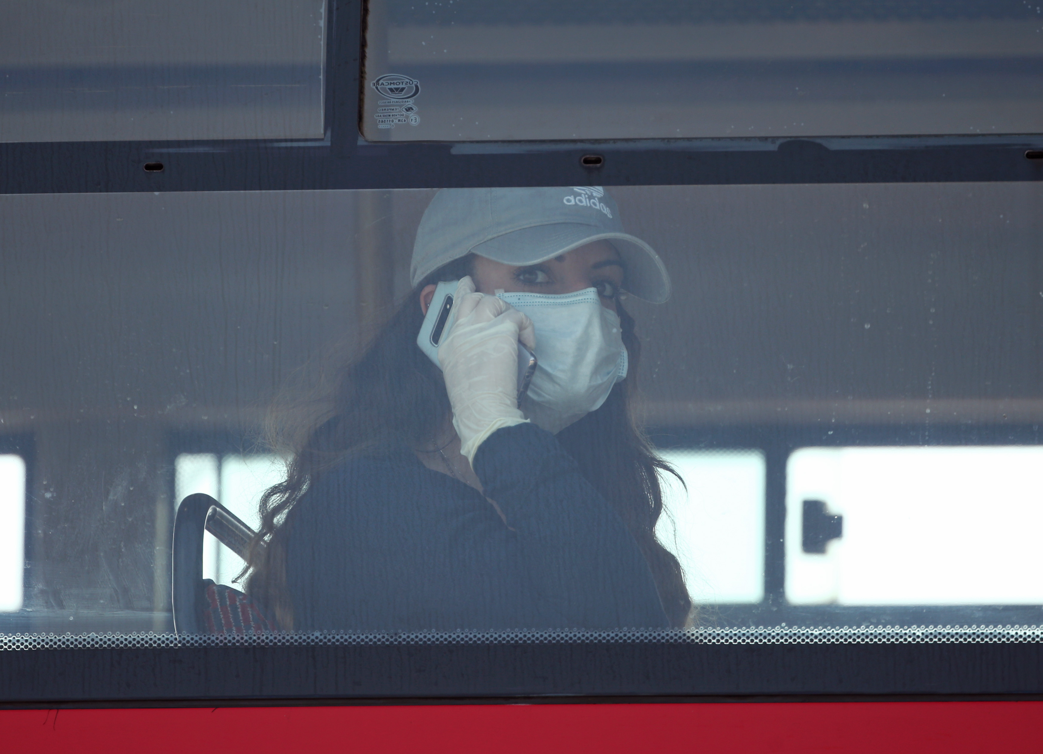 A woman on a bus wearing a face mask and latex gloves on Westminster Bridge, London, as the UK continues in lockdown to help curb the spread of the coronavirus. (Photo by Yui Mok/PA Images via Getty Images)