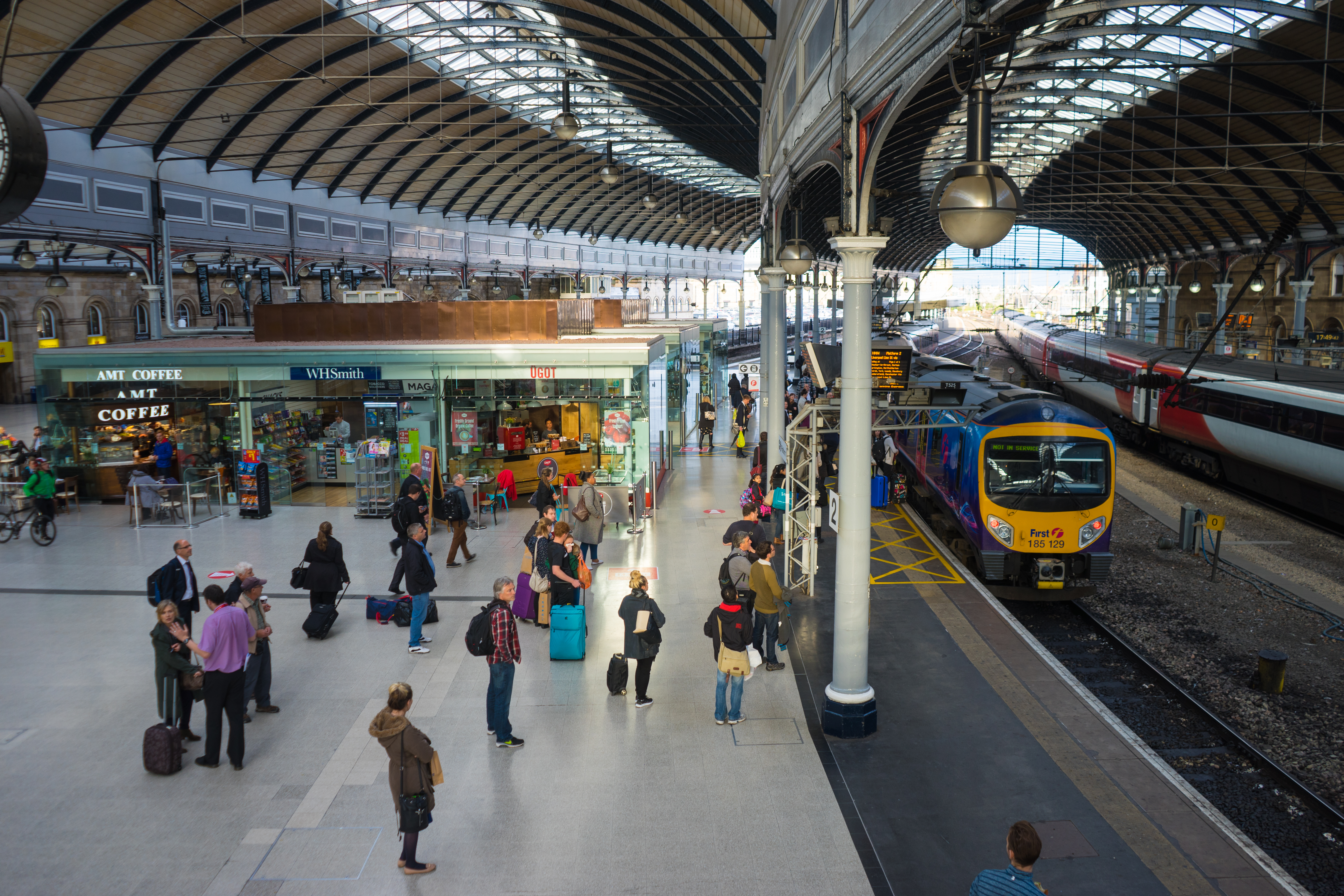 Newcastle Upon Tyne, UK, England - September 15, 2015:  People commuting over the main platform of Newcastle Central station, where a train awaits.