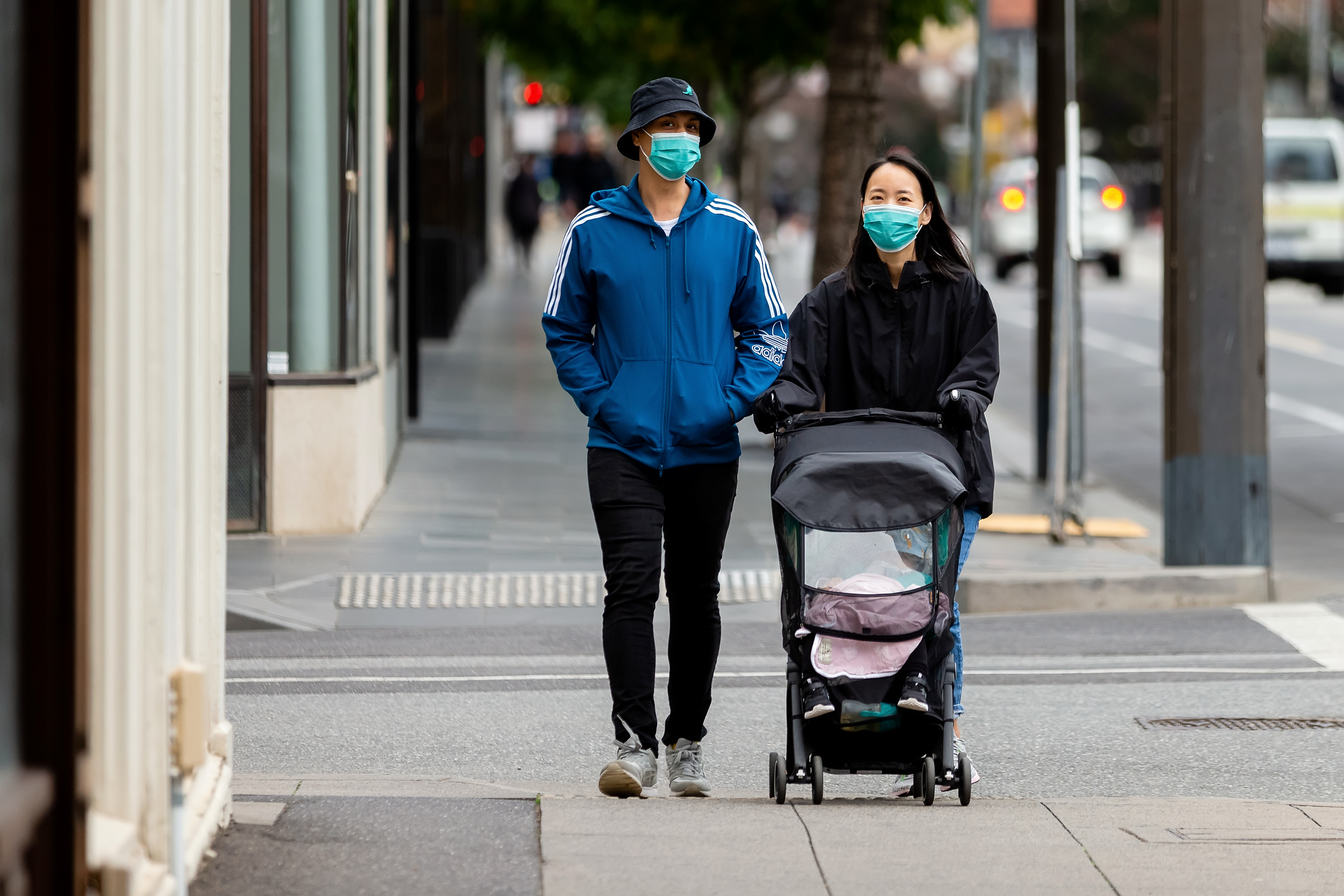 MELBOURNE, AUSTRALIA - APRIL 14: A couple walk down Chapel Street wearing masks during COVID 19 on 14 April, 2020 in Melbourne, Australia. (Photo by Speed Media/Icon Sportswire via Getty Images)