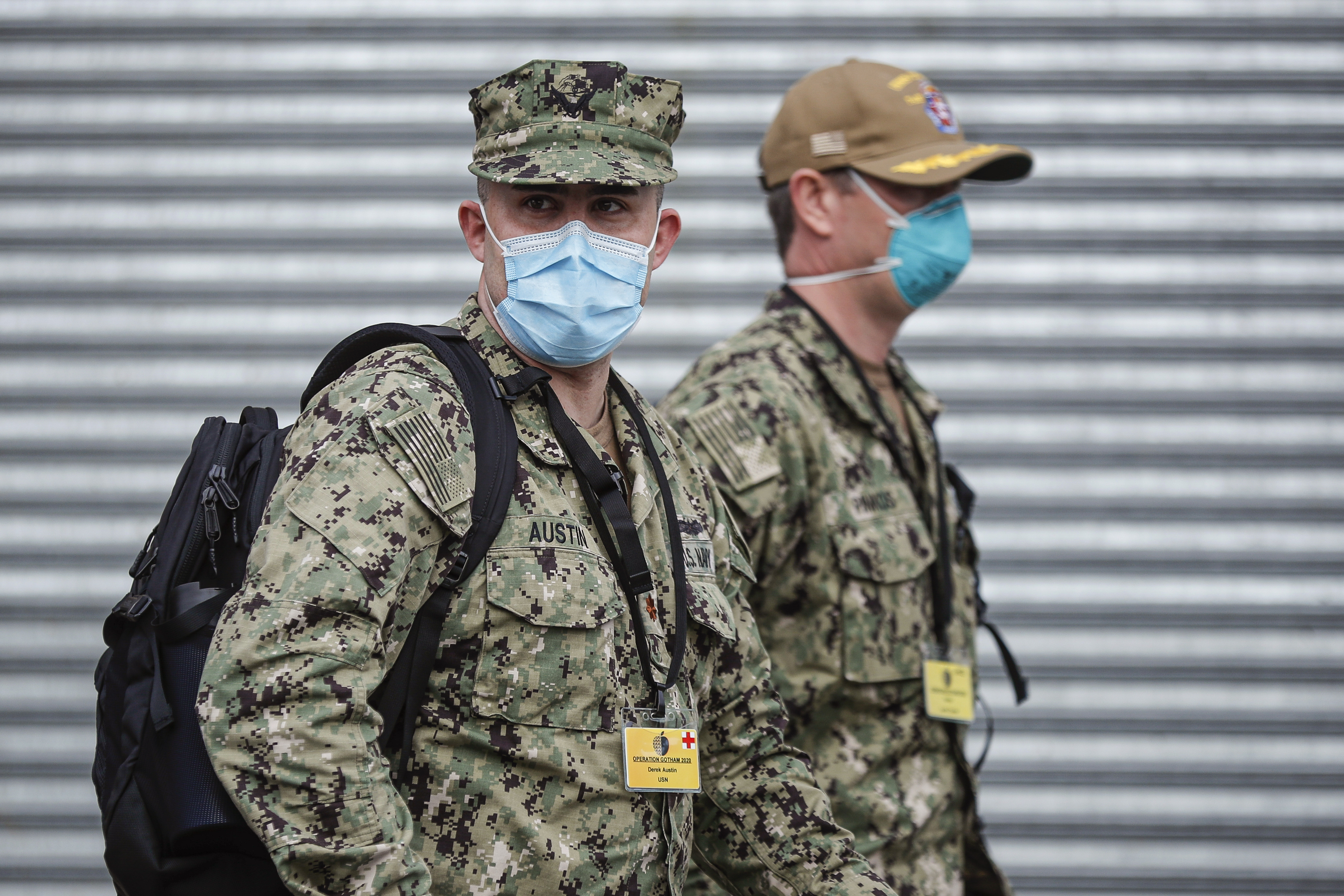 US Navy personnel wearing surgical masks to protect against the coronavirus, arrive at Wyckoff Heights Medical Center, Tuesday, April 7, 2020, in the Brooklyn borough of New York. The new coronavirus causes mild or moderate symptoms for most people, but for some, especially older adults and people with existing health problems, it can cause more severe illness or death. (AP Photo/John Minchillo)