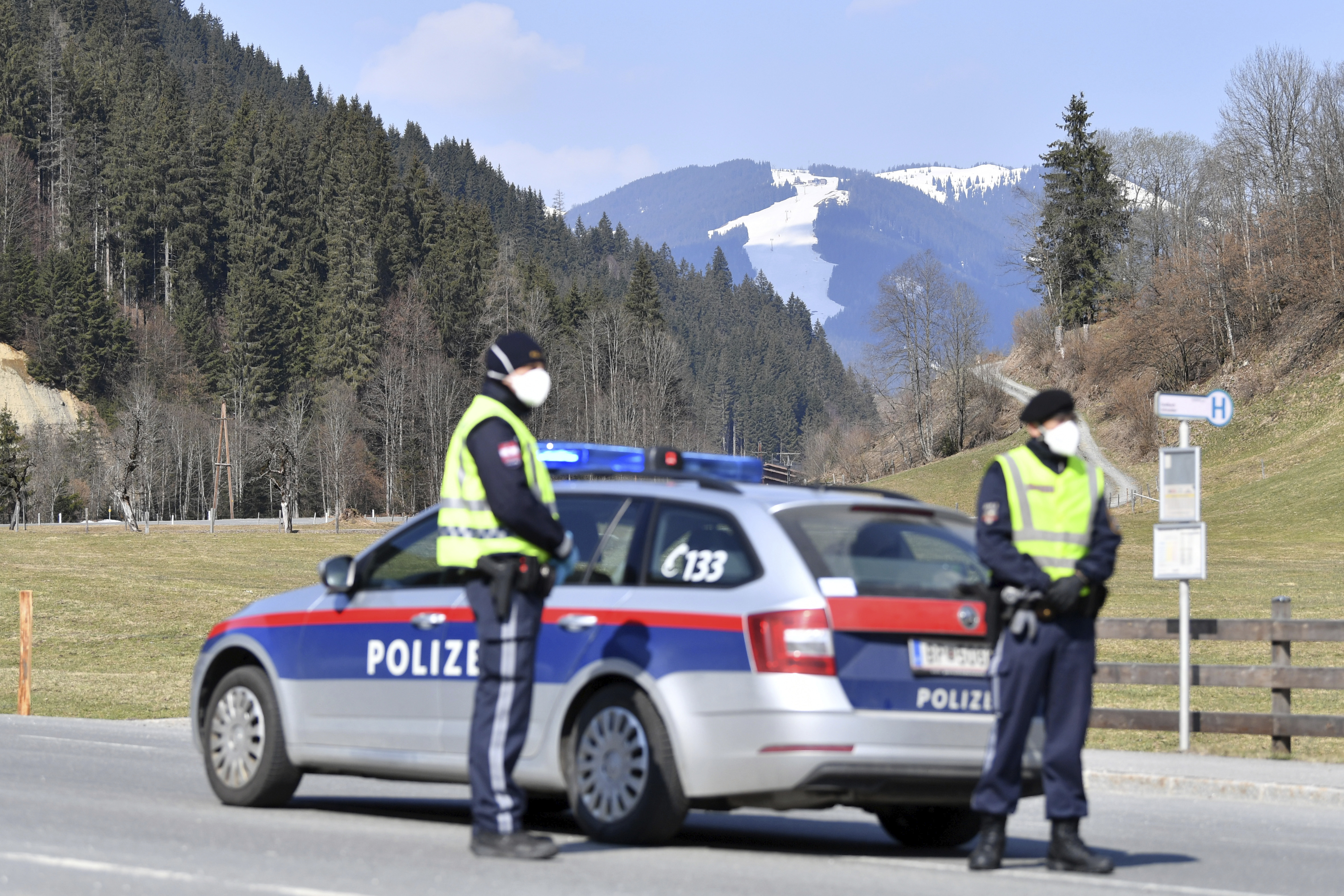 Police officers blog the road to the skying resort Saalbach Hinterglemm, Austrian province of Salzburg, Friday, April 3, 2020 after the city was quarantined.The Austrian government has moved to restrict freedom of movement for people, in an effort to slow the onset of the COVID-19 coronavirus. (AP Photo/Kerstin Joensson)