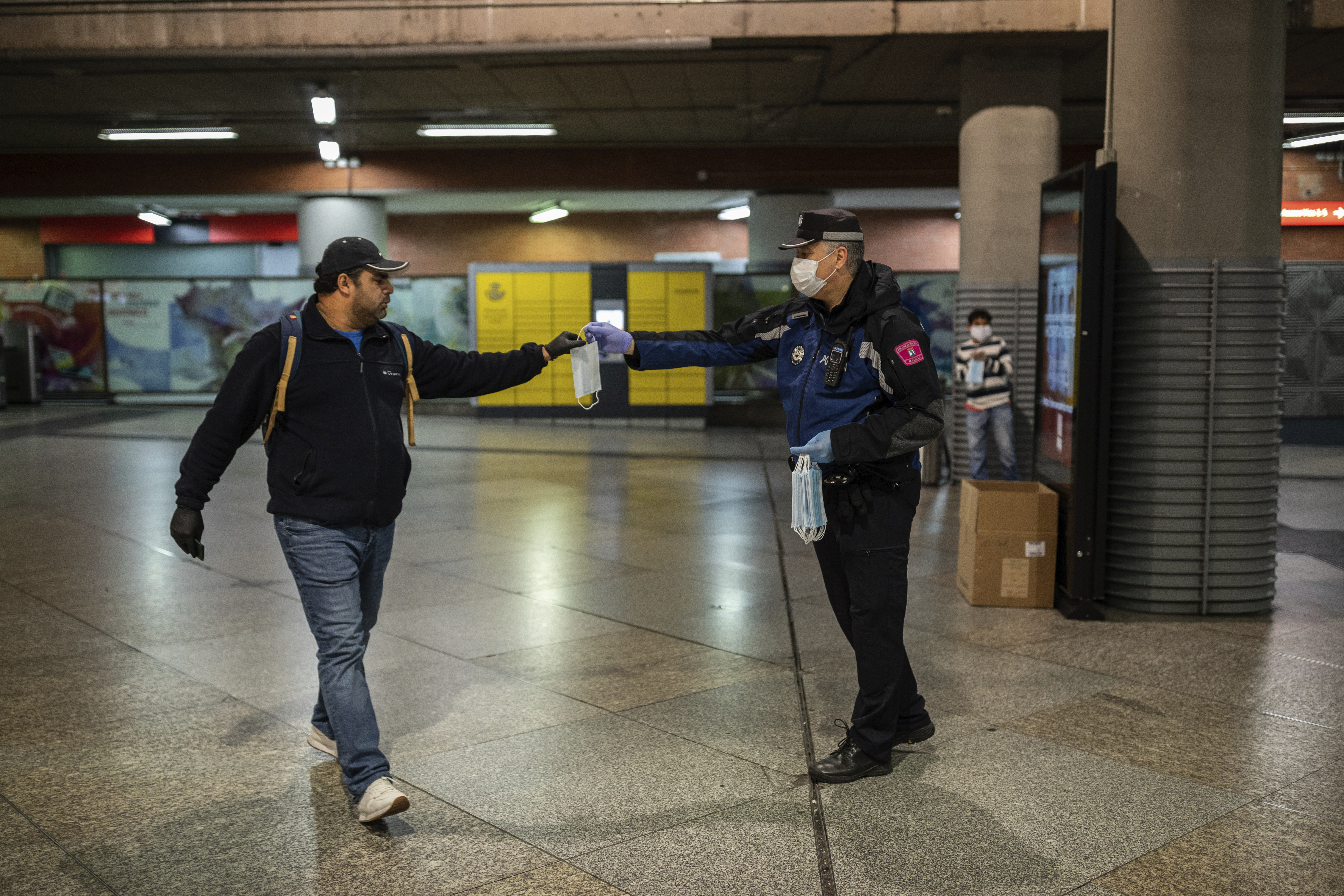 A local police distributes face masks to commuters at Atocha train station during the coronavirus outbreak in Madrid, Spain, Monday, April 13, 2020. Confronting both a public health emergency and long-term economic injury, Spain is cautiously re-starting some business activity to emerge from the nationwide near-total freeze that helped slow the country's grim coronavirus outbreak. The new coronavirus causes mild or moderate symptoms for most people, but for some, especially older adults and people with existing health problems, it can cause more severe illness or death. (AP Photo/Bernat Armangue)