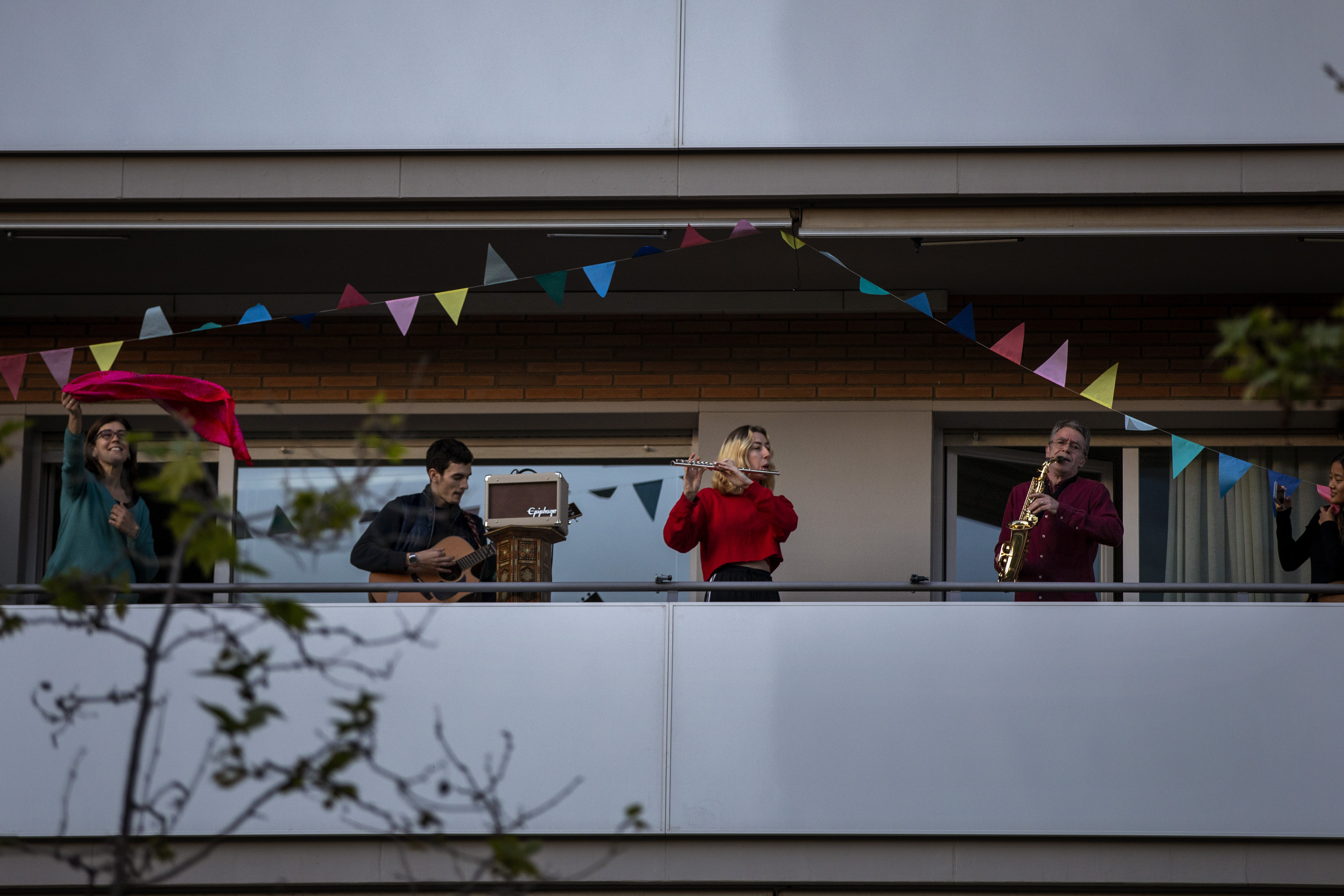 """Family members play their instruments performing the song """"Aleluya"""" on their balcony in support of the medical staff that are working on the COVID-19 virus outbreak in Barcelona, Spain, Sunday, April 5, 2020. Spanish Prime Minister Pedro Sanchez announced that he would ask the Parliament to extend the state of emergency by two more weeks, taking the lockdown on mobility until April 26. The new coronavirus causes mild or moderate symptoms for most people, but for some, especially older adults and people with existing health problems, it can cause more severe illness or death. (AP Photo/Emilio Morenatti)"""
