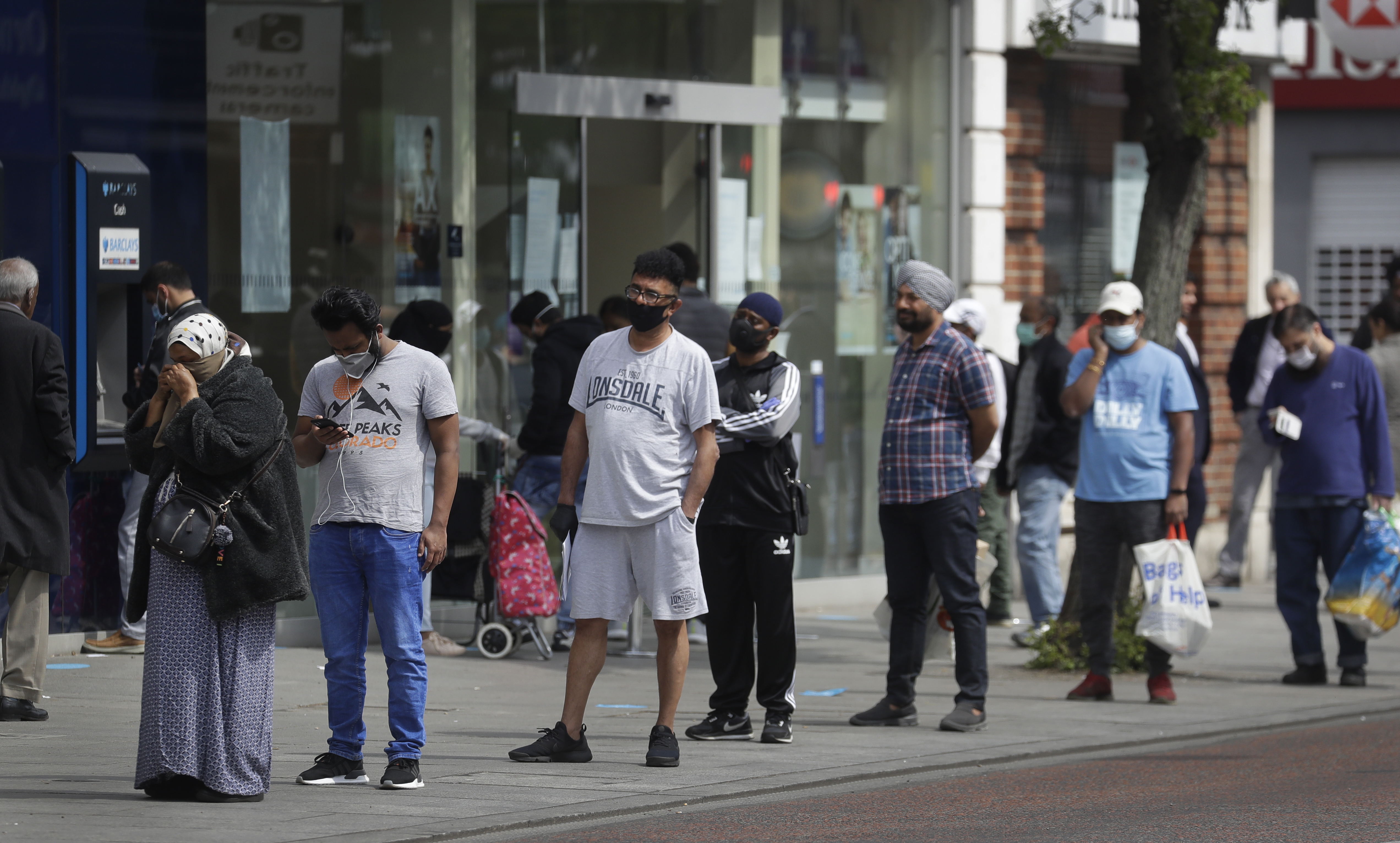 People social distance as they queue to enter a shop on a high street, as the country continues its lockdown to help curb the spread of the virus, in London, Monday, April 27, 2020. While Britain is still in lockdown, some nations have begun gradually easing coronavirus lockdowns, each pursuing its own approach but all with a common goal in mind, restarting their economies without triggering a new wave of infections. (AP Photo/Kirsty Wigglesworth)