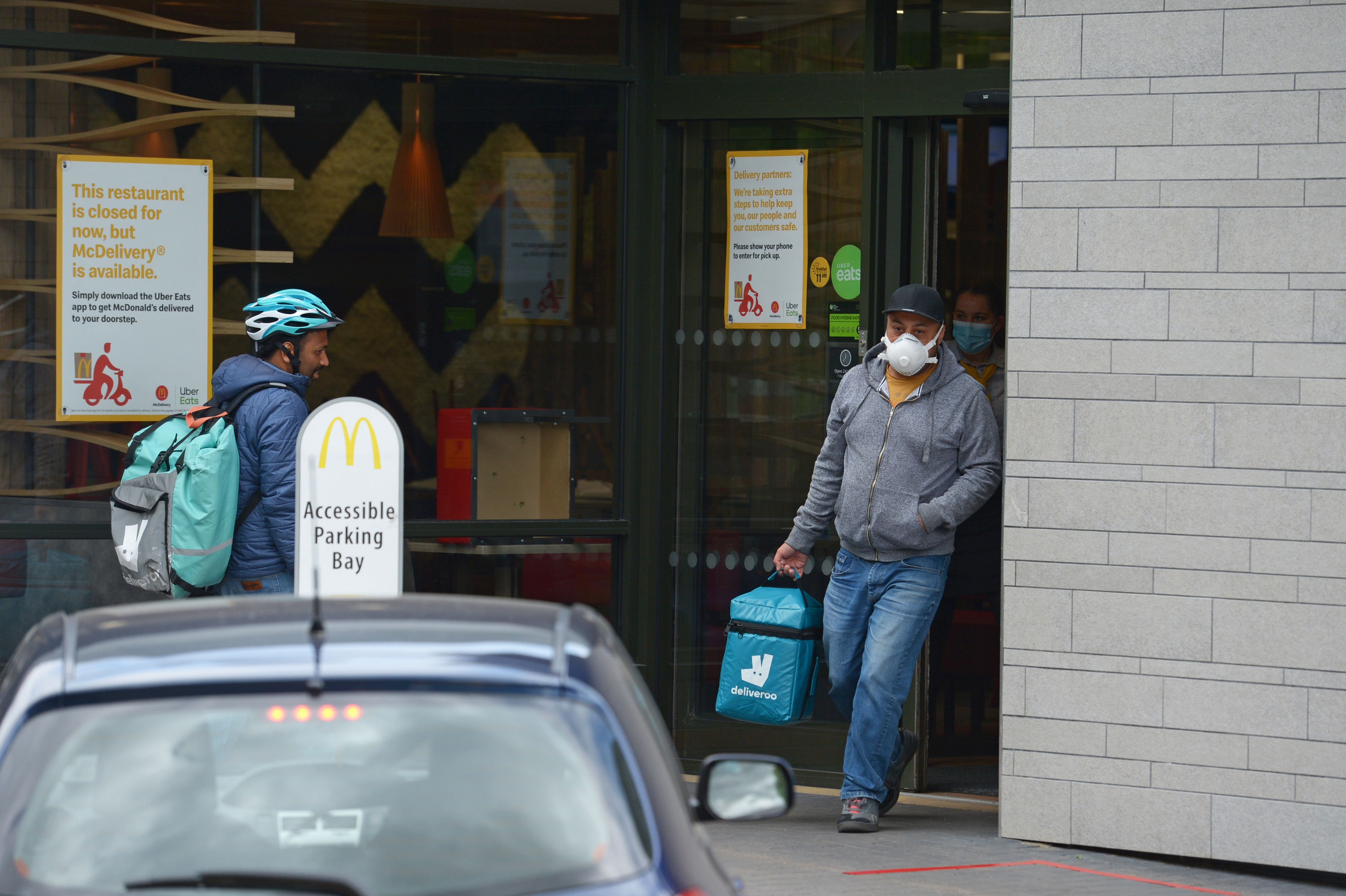 Deliveroo workers at a branch of McDonald's in Boreham, Chelmsford, Essex, one of 15 of the restaurant chain locations to have reopened for takeaway.