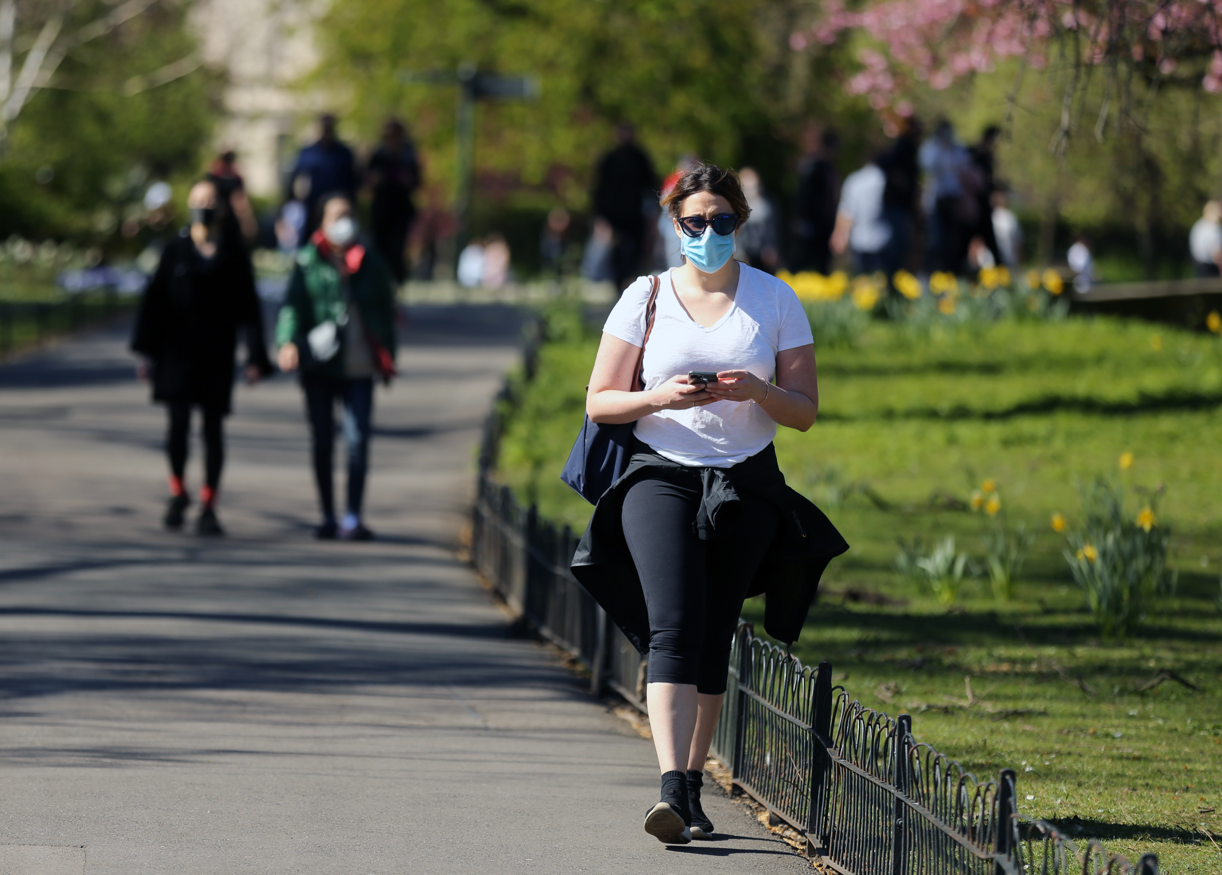A woman wearing protective face masks enjoys the warm weather at Regent's Park, North London, as the UK continues in lockdown to help curb the spread of the coronavirus