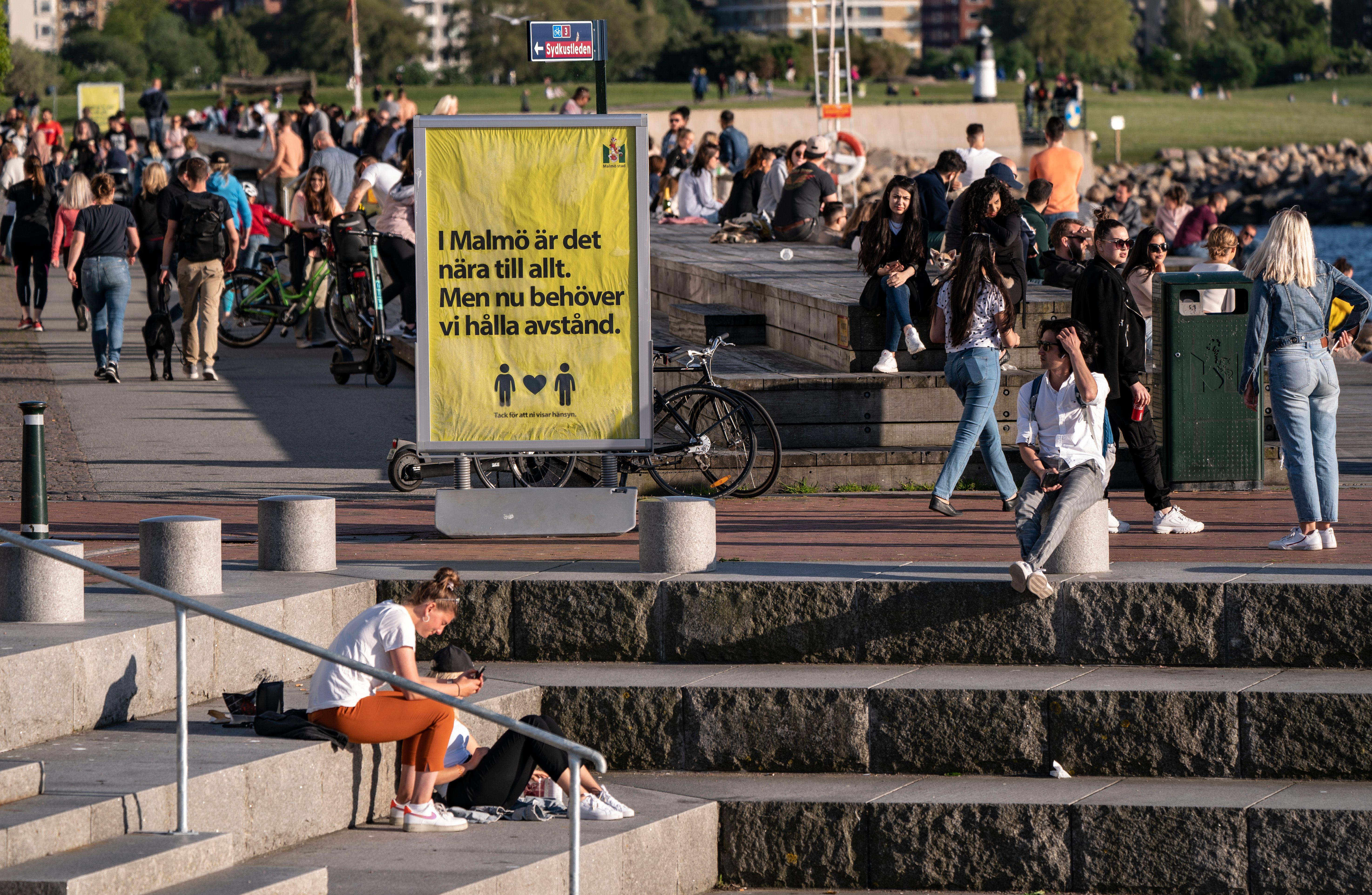 People enjoy the warm evening at Sundspromenaden in Malmo, Sweden, on May 26, 2020, amid the coronavirus pandemic. - The sign reads 'In Malmo everything is near. But now, we need to keep distance'. (Photo by Johan NILSSON / TT News Agency / AFP) / Sweden OUT (Photo by JOHAN NILSSON/TT News Agency/AFP via Getty Images)