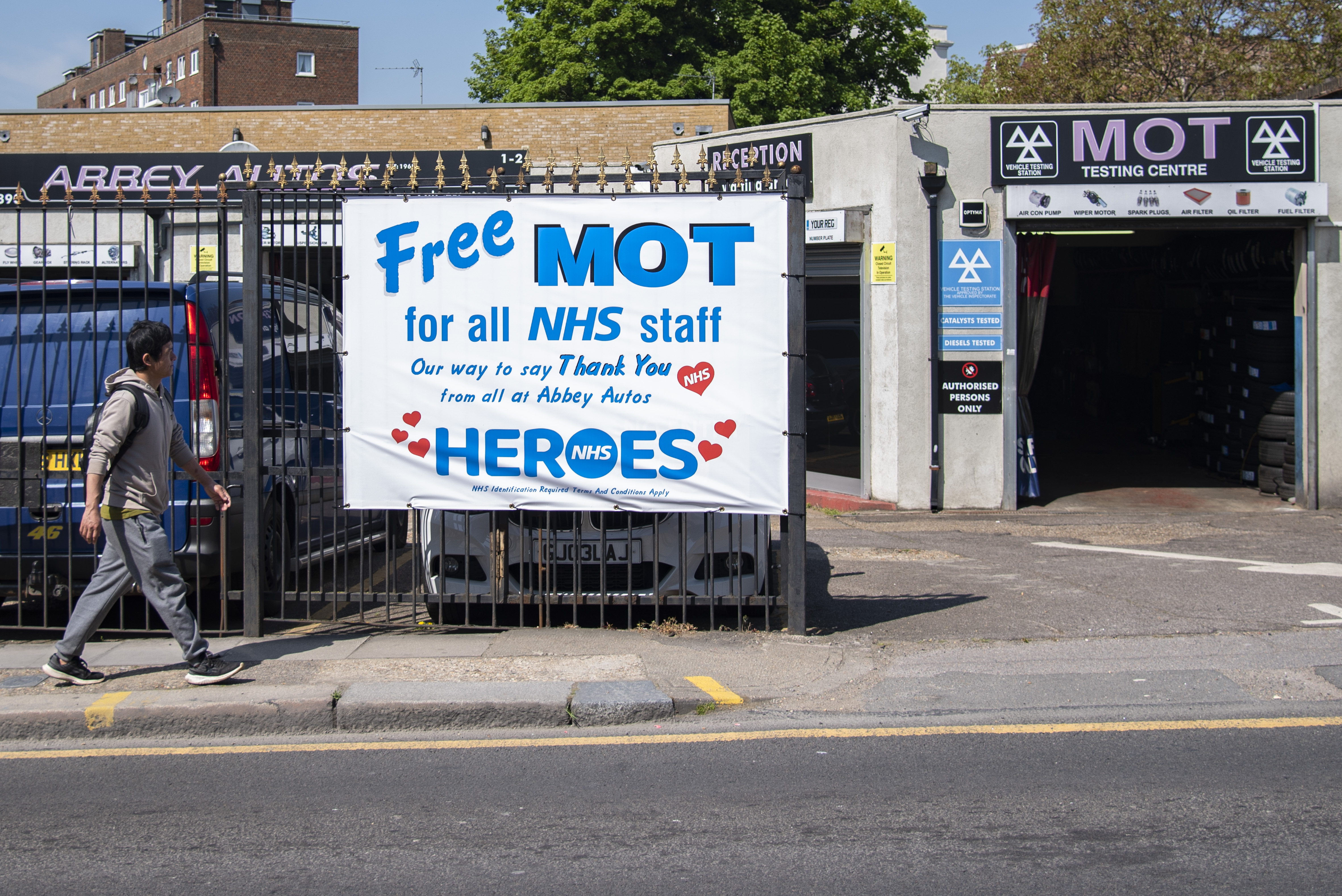 A man walks past a garage offering free MOT's for all NHS (National Health Service) staff on 23th April 2020 in London, United Kingdom.There have been almost 133,495 reported cases of the COVID-19 coronavirus in the United Kingdom and almost 19,000 deaths. The country is in its fifth week of lockdown measures aimed at slowing the spread of the virus. (photo by Claire Doherty/In Pictures via Getty Images)