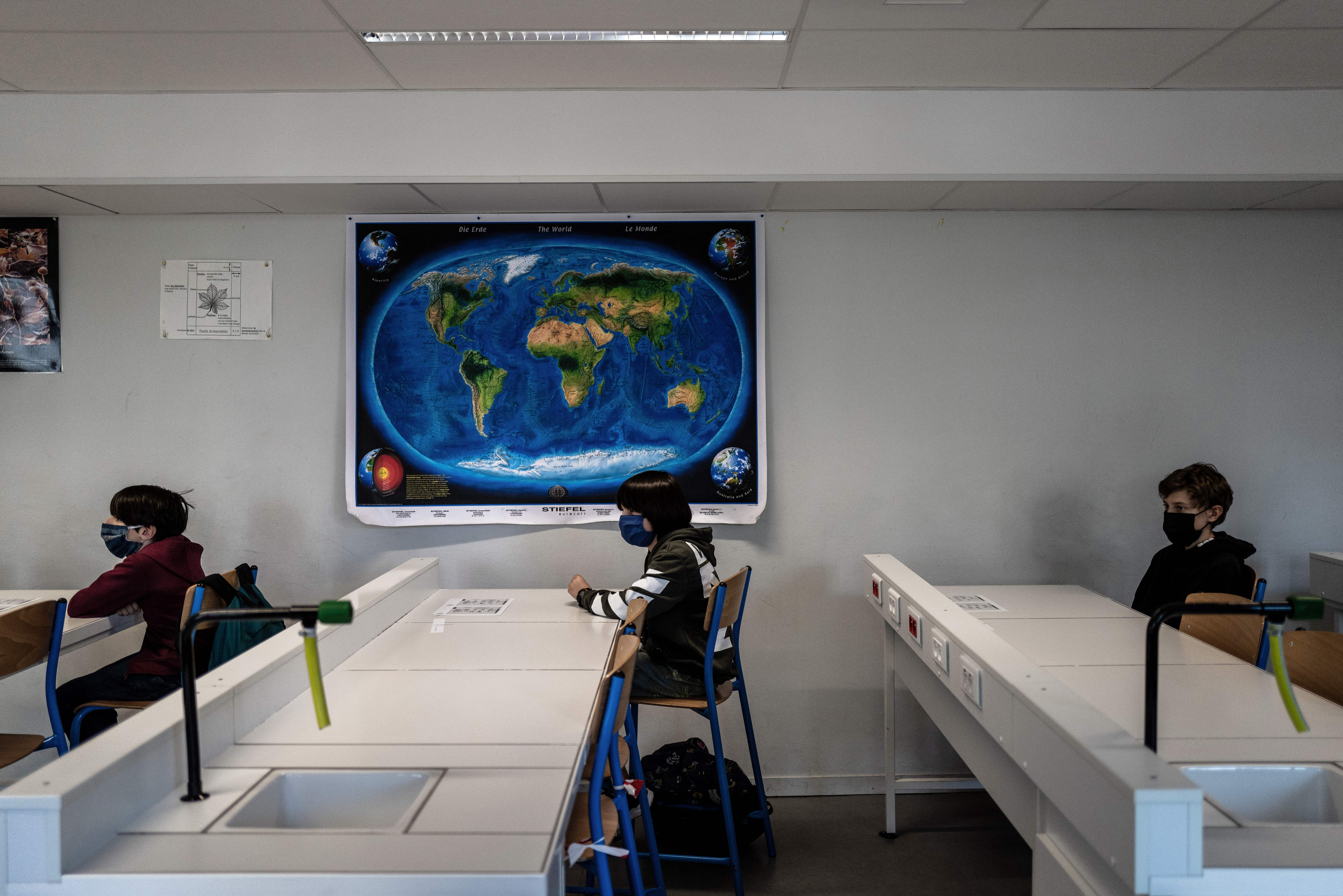 Schoolchildren wearing protective face masks attend a lesson in a middle school classroom, on May 18, 2020 in Lyon, central eastern France, after France eased lockdown measures to curb the spread of the COVID-19 pandemic, caused by the novel coronavirus. (Photo by JEFF PACHOUD / AFP) (Photo by JEFF PACHOUD/AFP via Getty Images)