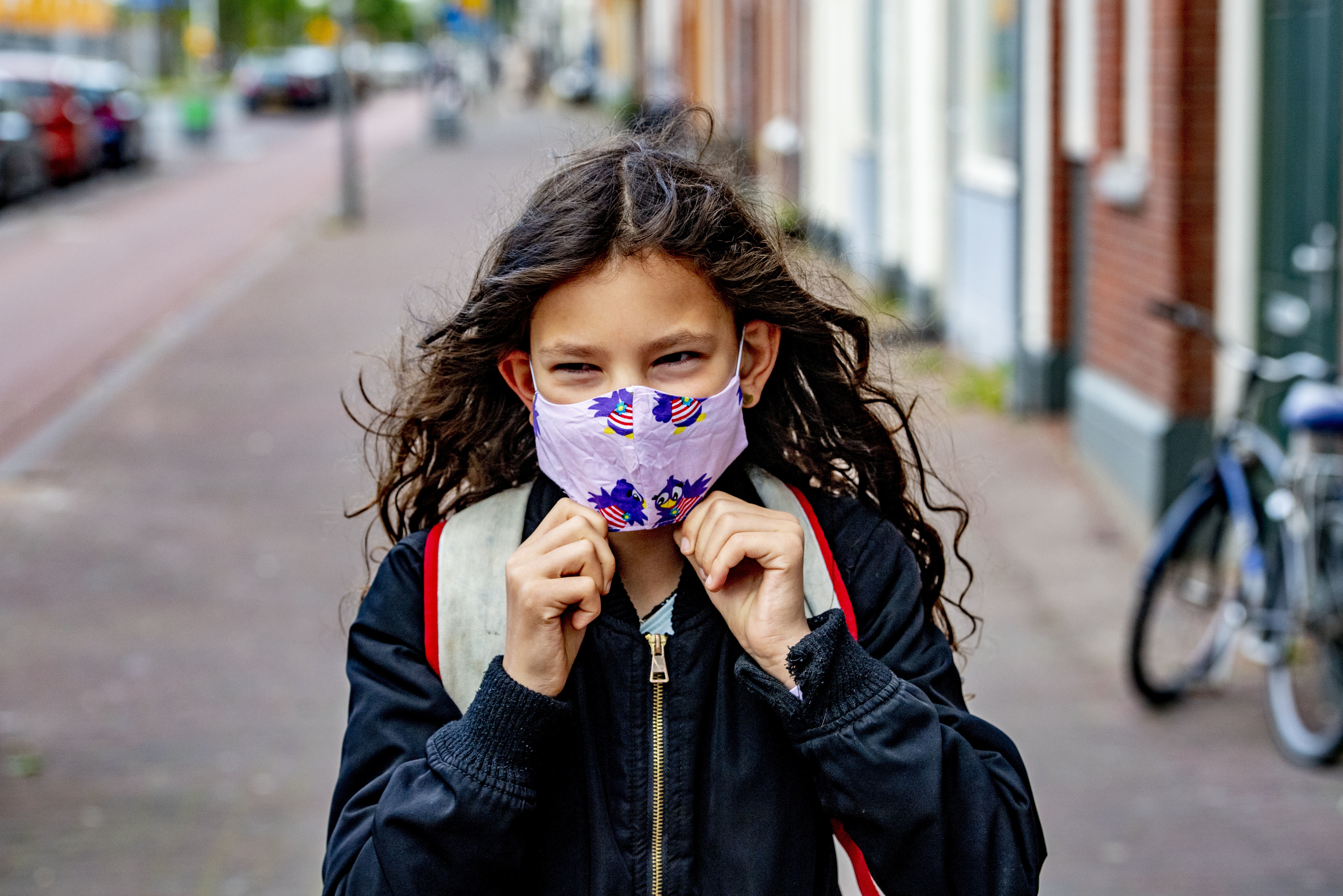 ROTTERDAM, NETHERLANDS - 2020/05/11: A kid going to school while wearing a face mask as a preventive measure against the spread of Coronavirus (COVID-19) crisis. Children go back to school in the Rotterdam district of Katendrecht, after the Coronavirus (COVID-19) lockdown crisis for half days. (Photo by Robin Utrecht/SOPA Images/LightRocket via Getty Images)