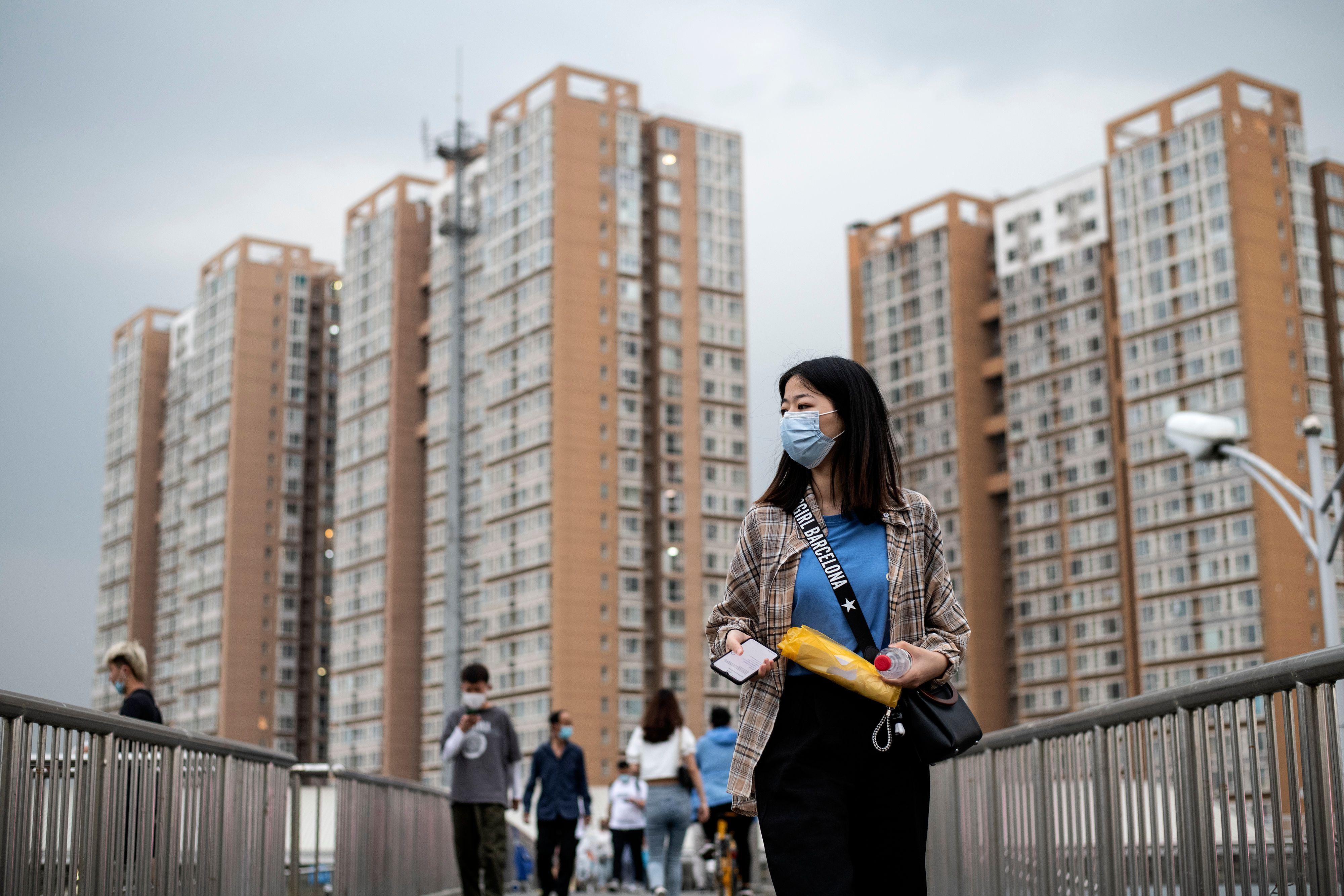 People wearing facemasks walk on an overpass in Beijing on June 1, 2020. (Photo by Noel CELIS / AFP) (Photo by NOEL CELIS/AFP via Getty Images)