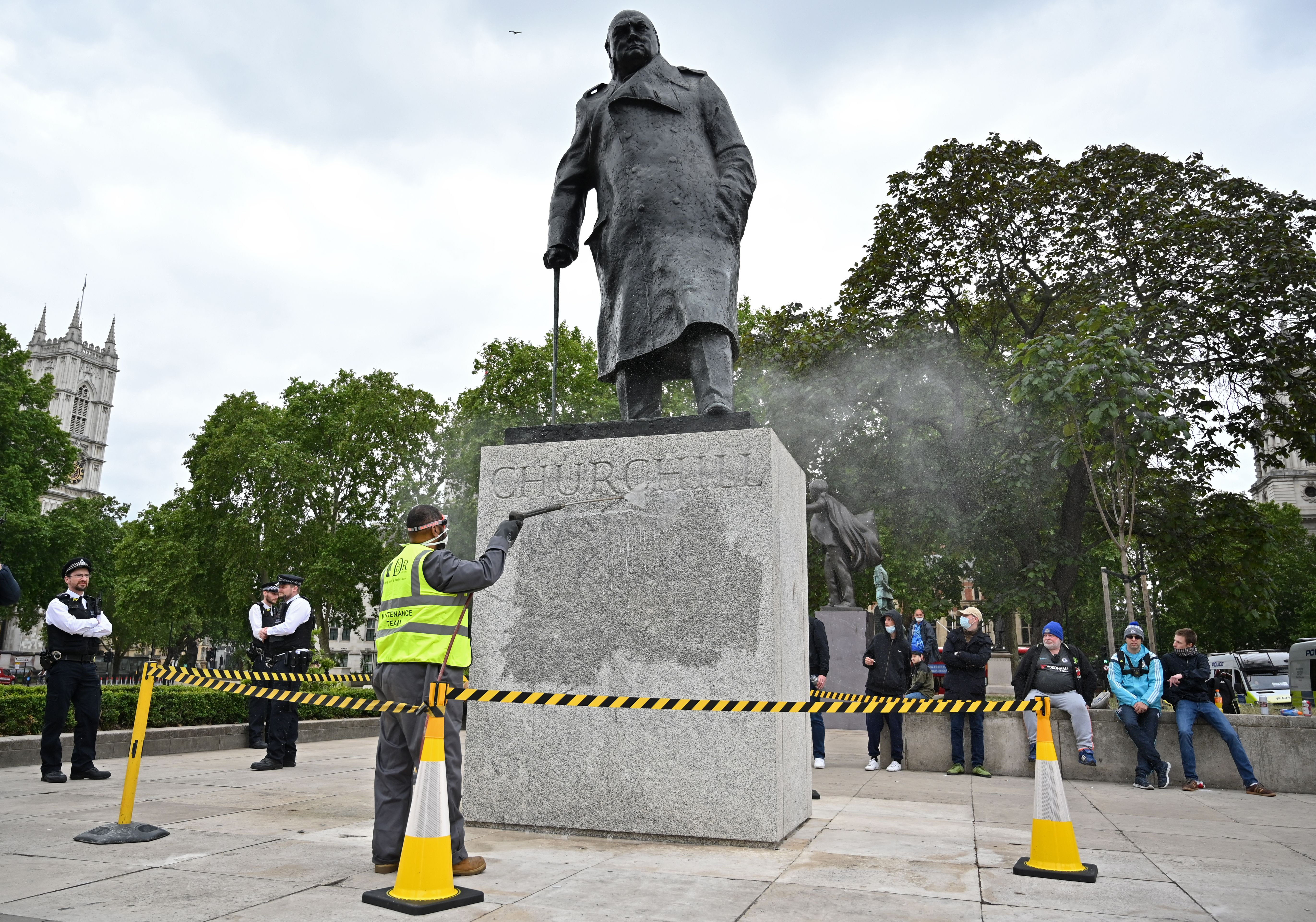 """The statue of former British prime minister Winston Churchill is cleaned in Parliament Square, central London on June 8, 2020, after being defaced, with the words (Churchill) """"was a racist"""" written on it's base by protesters at a demonstration on June 7, 2020, organised to show solidarity with the Black Lives Matter movement. - Most marches at the weekend were peaceful but there were flashes of violence, including in London, where the statue of World War II leader Winston Churchill in Parliament Square was defaced. (Photo by JUSTIN TALLIS / AFP) (Photo by JUSTIN TALLIS/AFP via Getty Images)"""