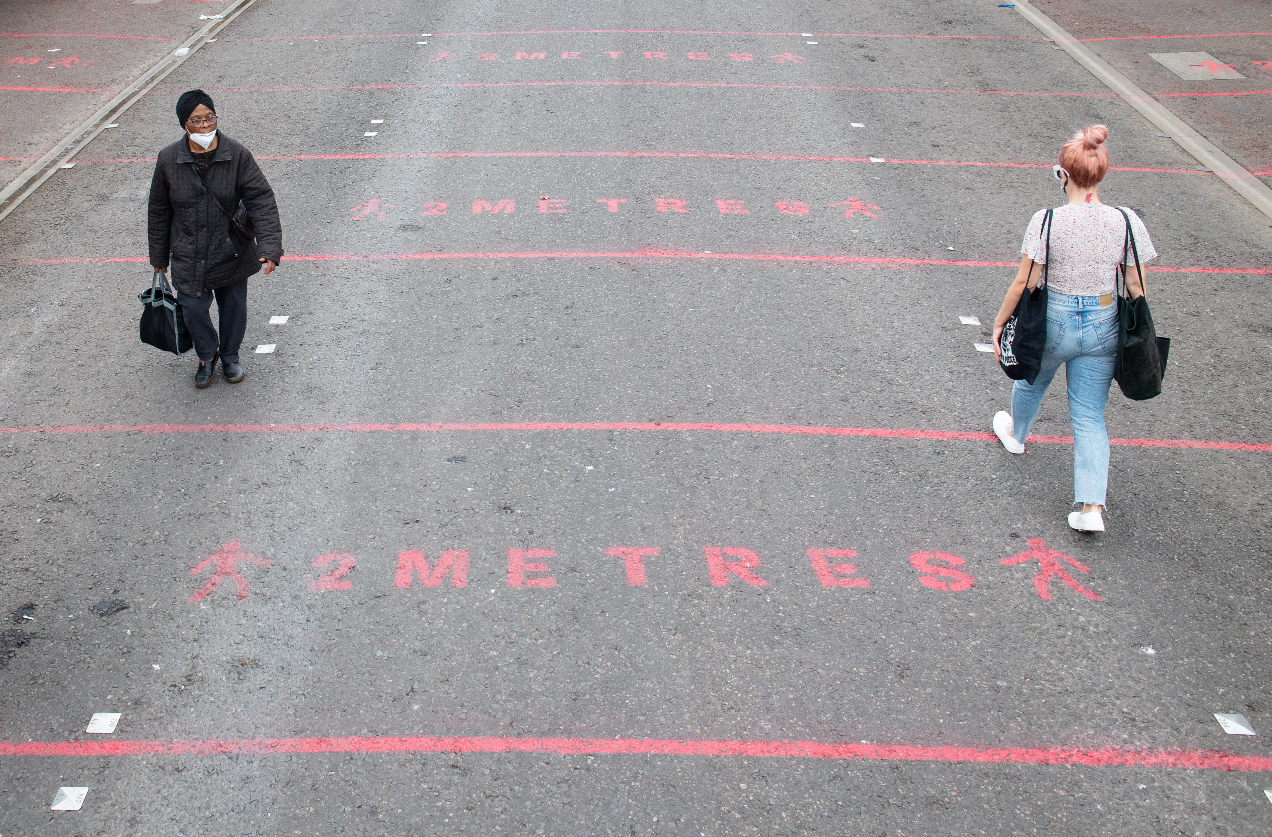 """People walk over two metre social distancing markings at Ridley Road street market in east London, as the government considers relaxing official guidelines on social distancing to a shorter distance of one metre. Health Secretary Matt Hancock, pressed to reduce social distancing from two metres to one metre, has told the Commons: """"It's the sort of thing of course we want to lift and we need to do that in a way that is careful and safe."""