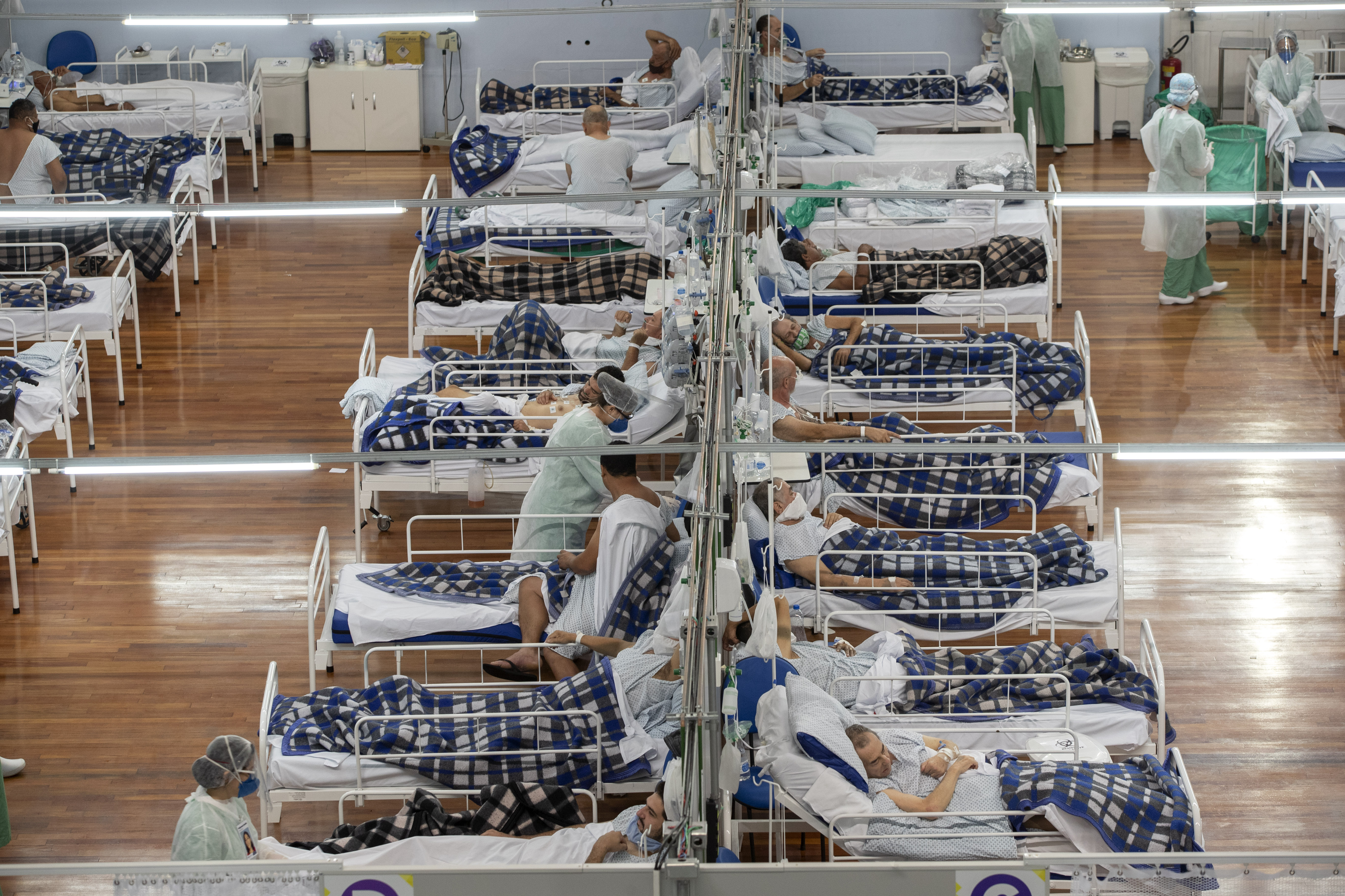 COVID-19 patients lie on beds in a field hospital built inside a gym in Santo Andre, on the outskirts of Sao Paulo, Brazil, Tuesday, June 9, 2020. (AP Photo/Andre Penner)