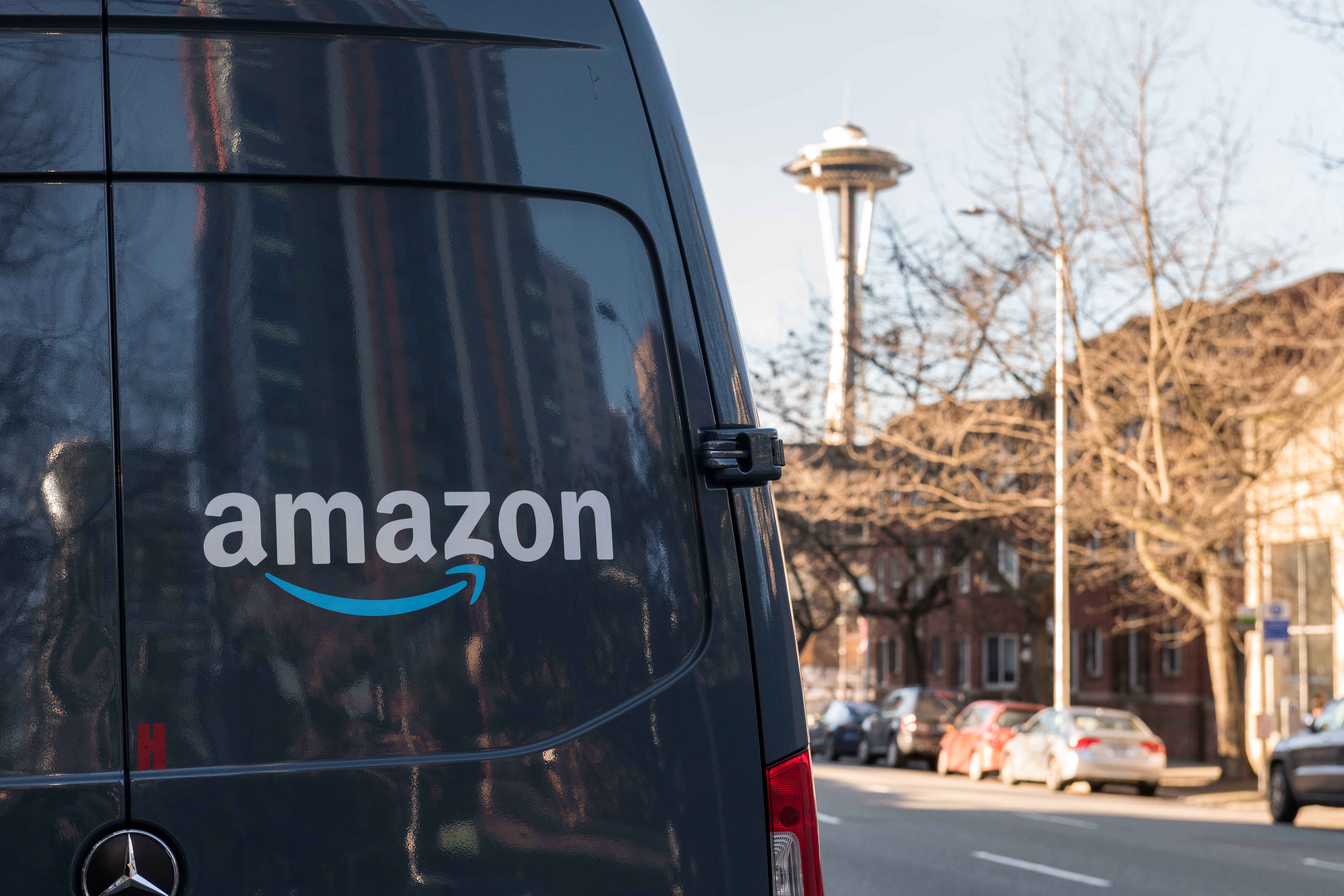 Seattle, USA - Feb 10, 2020: Amazon Prime Now Delivery van on 4th avenue late in the day with the Space Needle in the background.
