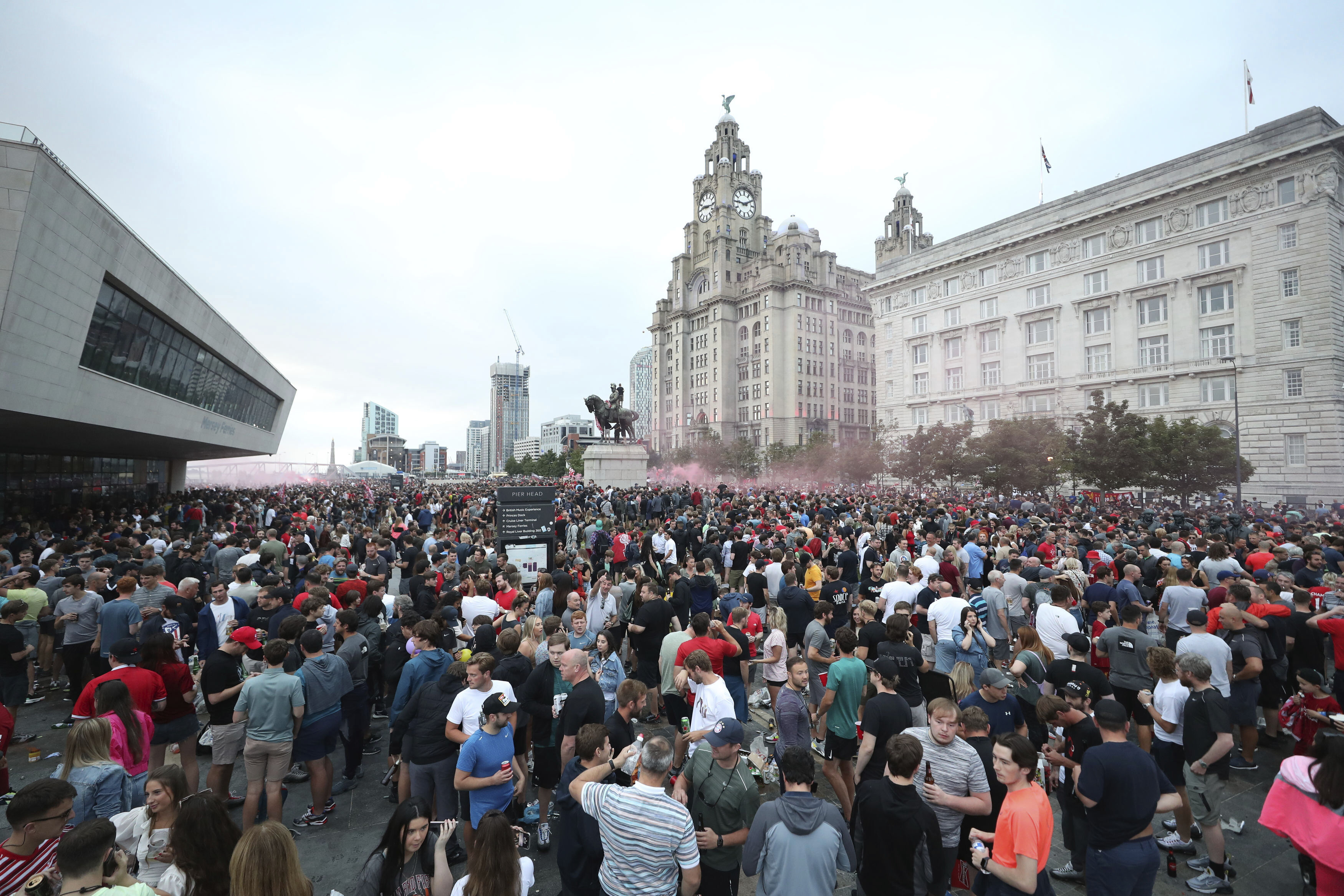 Liverpool soccer fans let off flares outside the Liver Building in Liverpool, England, Friday, June 26, 2020. Fans are being urged to celebrate the club's Premier League triumph at home as police believe more gatherings are planned after thousands filled the streets outside Anfield stadium. (Peter Byrne/PA via AP)