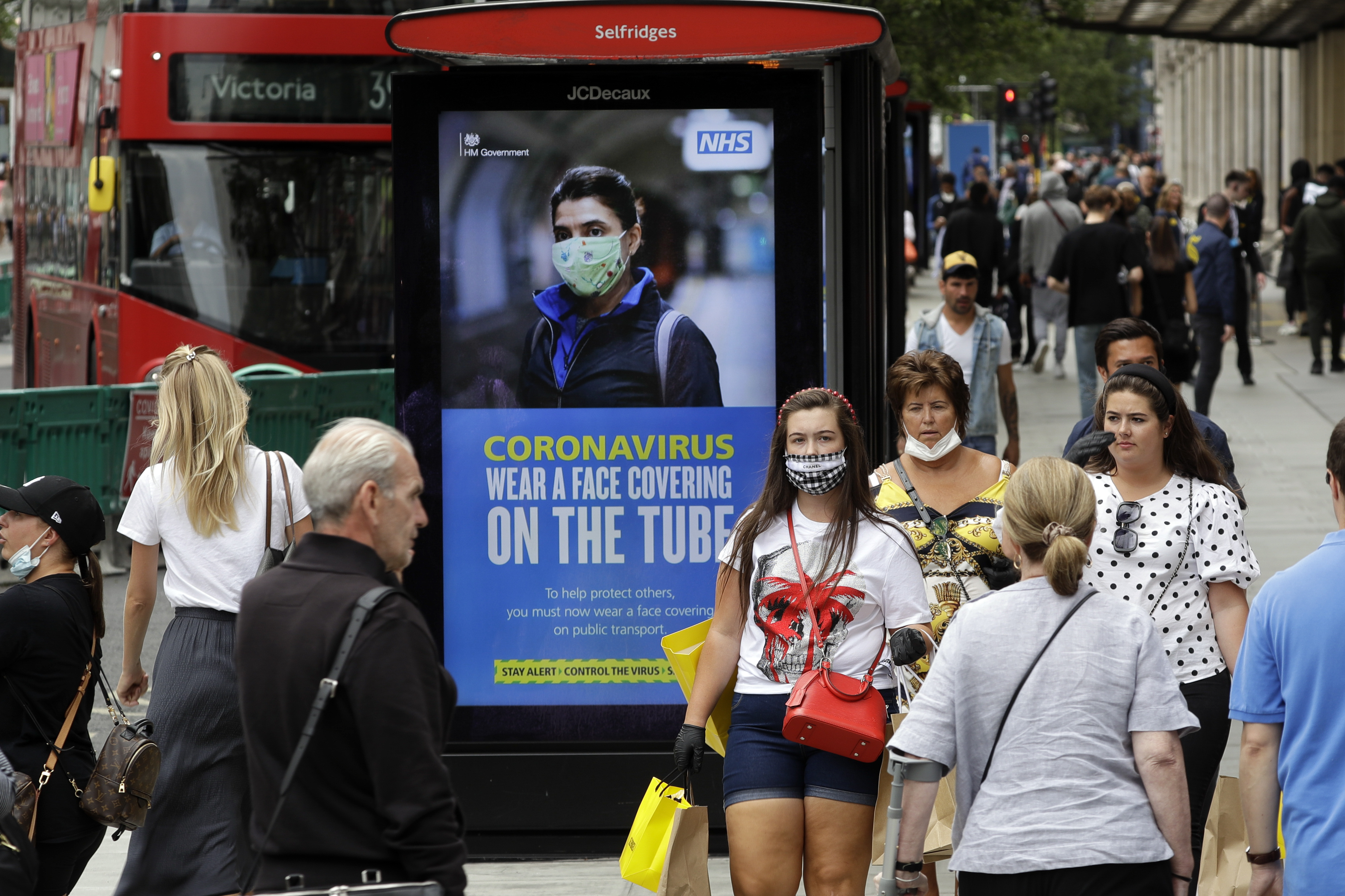People walk by a COVID-19 infection awareness poster in London, Monday, June 15, 2020. After three months of being closed under coronavirus restrictions, shops selling fashion, toys and other non-essential goods are being allowed to reopen across England for the first time since the country went into lockdown in March.(AP Photo/Matt Dunham)