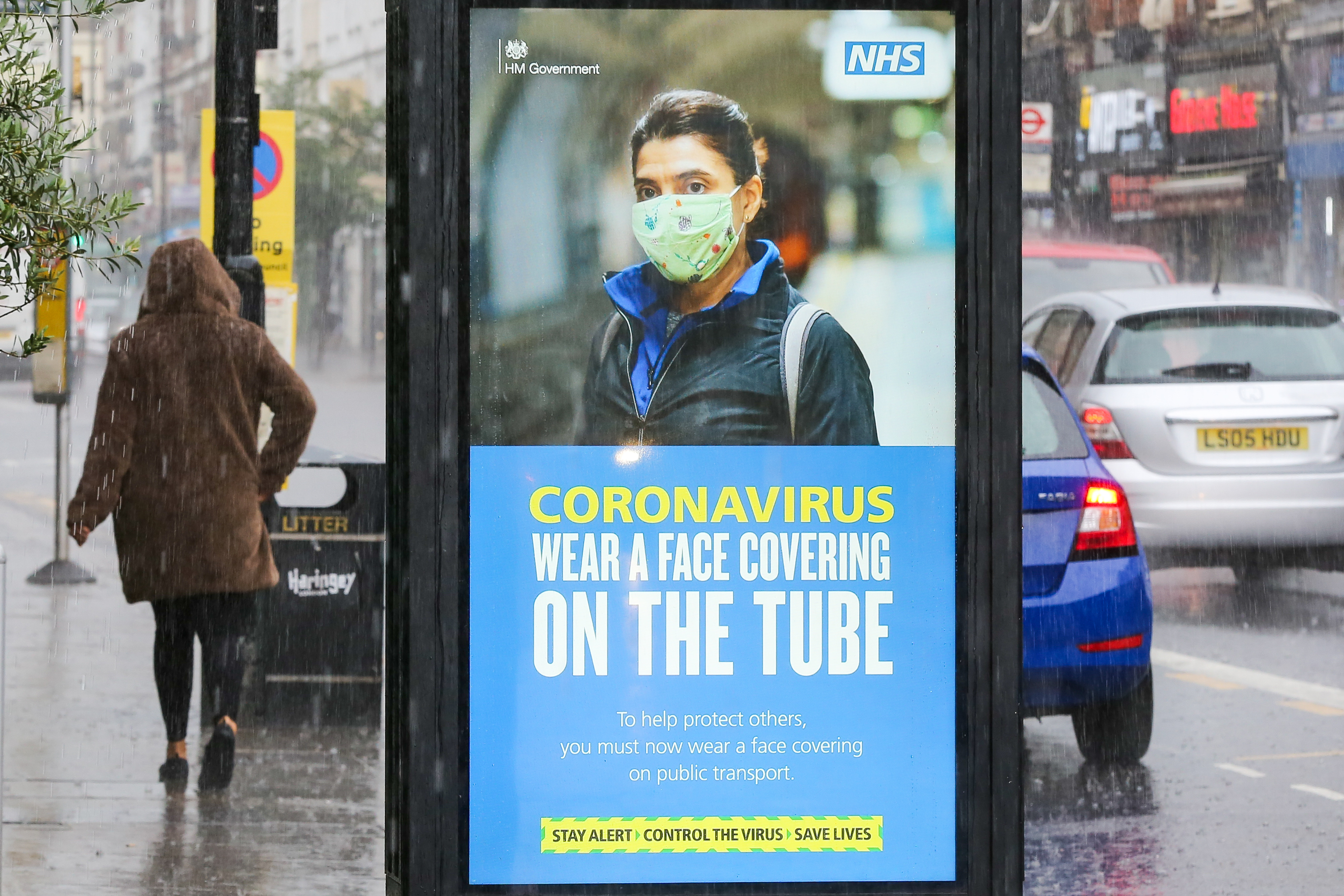 A woman walks past a face mask awareness billboard on a coronavirus public information campaign by Transport for London. (Photo by Dinendra Haria / SOPA Images/Sipa USA)