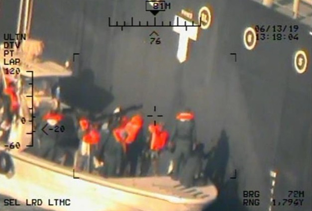 This image, taken from a U.S. Navy helicopter, shows what the Navy says are members of the Islamic Revolutionary Guard Corps Navy removing an unexploded limpet mine from the M/T Kokuka Courageous. (Photo: U.S. Department of Defense via AP)