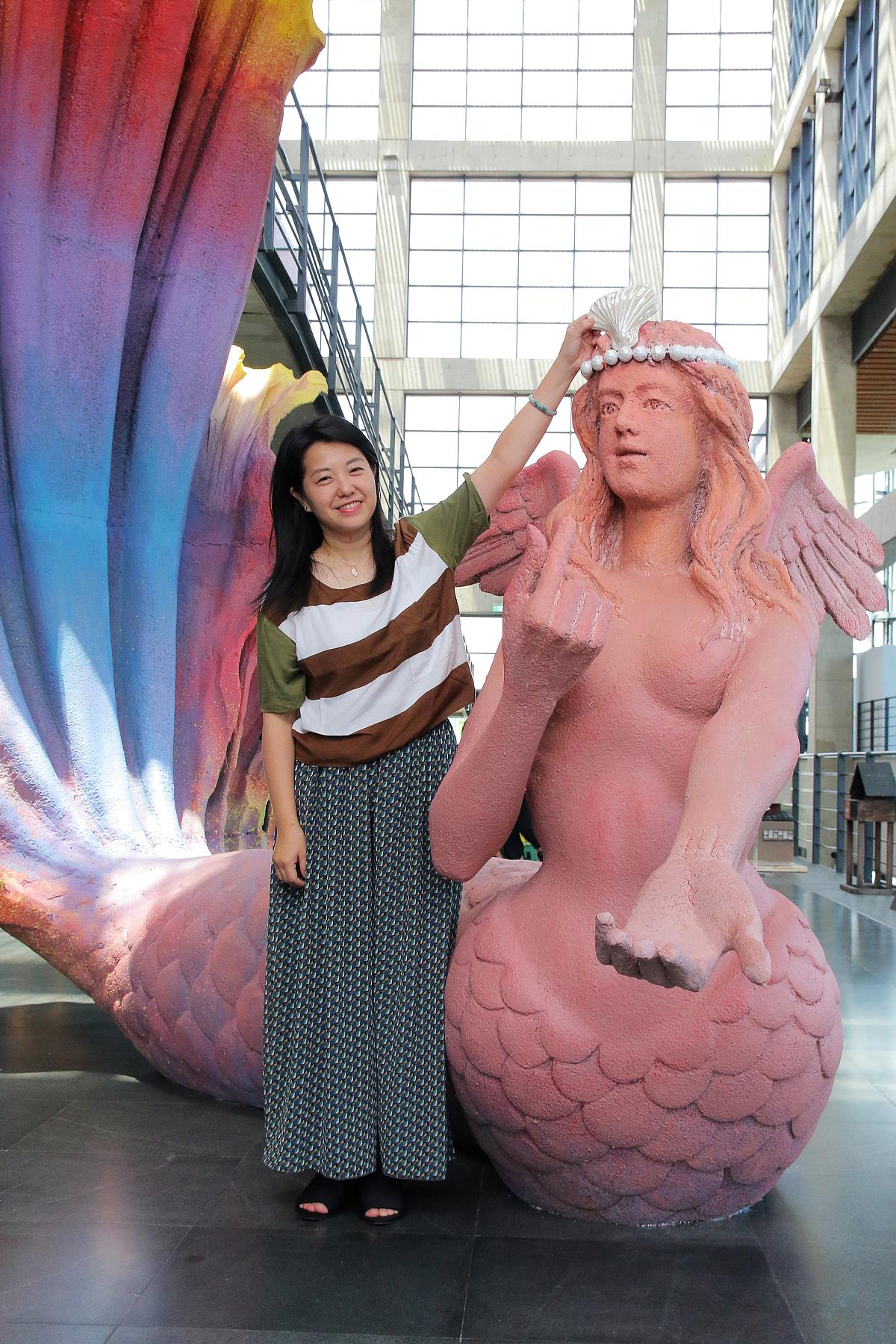 文化局長蔡佳芬把特製的陶瓷貝殼鑲在《我愛超級美人魚》的頭飾上 (圖片來源:鶯歌陶瓷博物館)