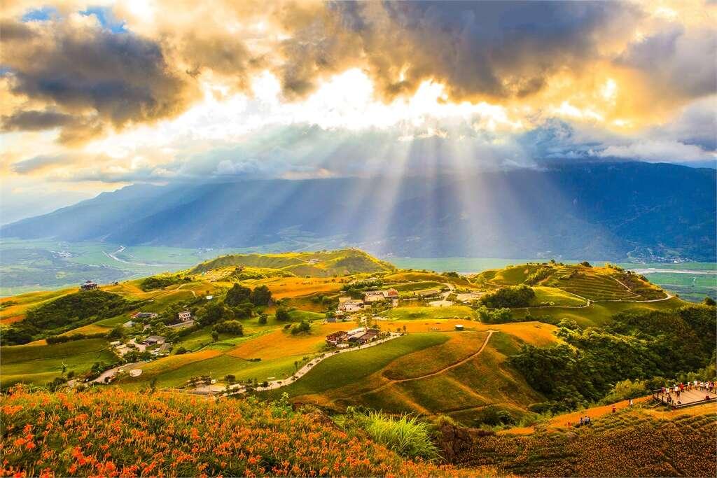 六十石山的招牌美景是夕陽與雲隙光搭配黃澄澄金針花海。圖/花東縱谷風景區