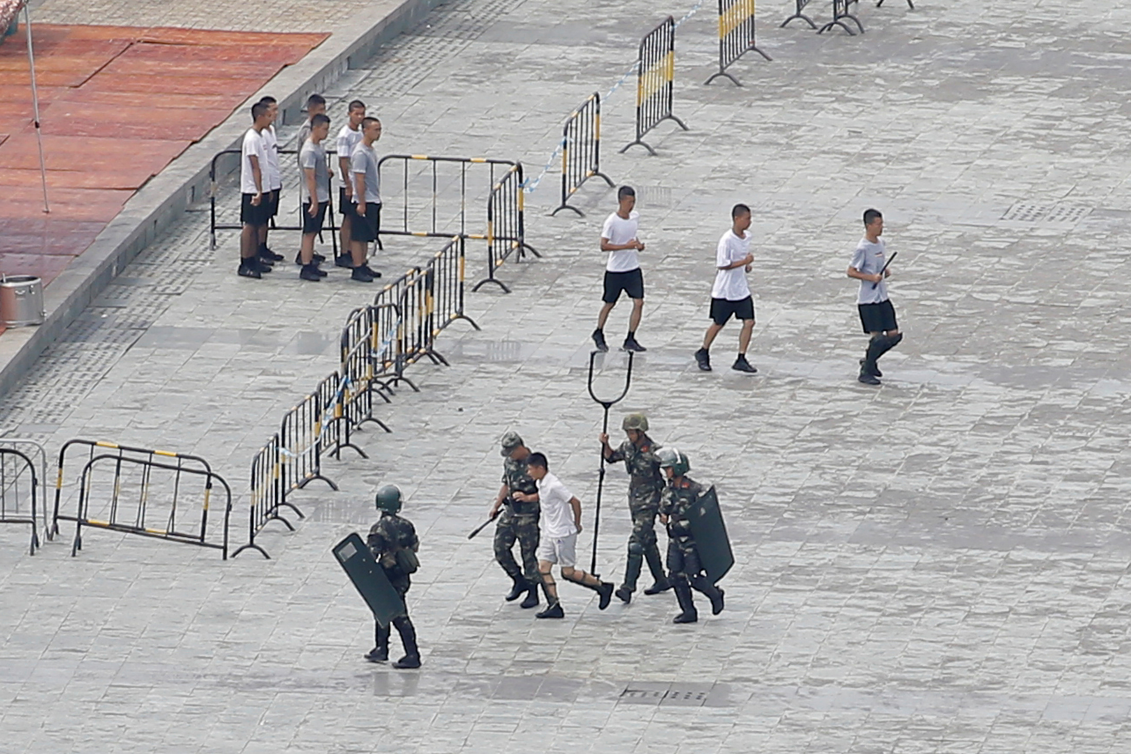 A man is escorted by armed officers during a drill at Shenzhen Bay Sports Centre. (Reuters)