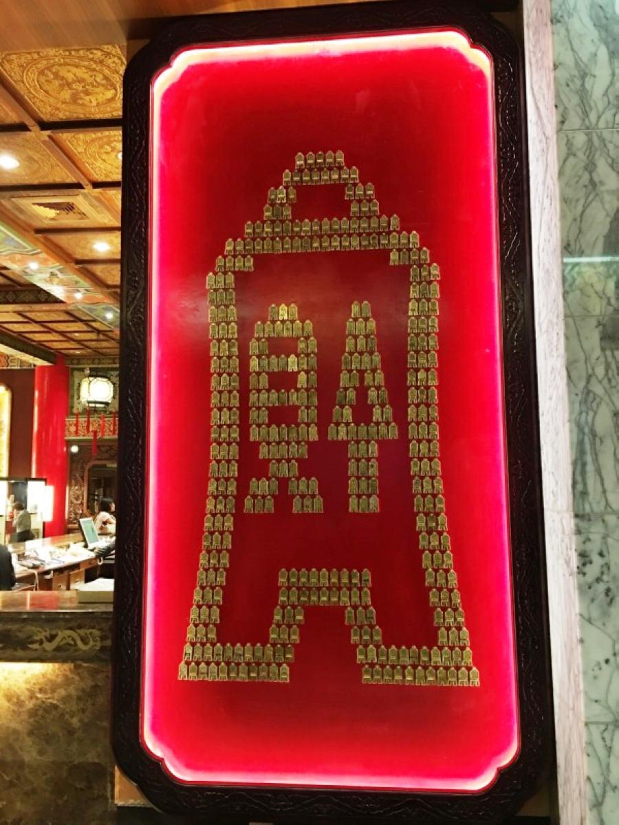 在飯店大廳右側,一座高400公分、寬209公分,由374個「功成身退」的「貨布」鑰匙牌組合而成的展示牆 (圖片來源:圓山大飯店)