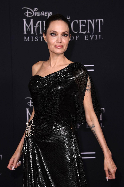 安潔莉娜裘莉Angelina Jolie則是選擇全黑的長裙禮服並搭配個性帥氣的尖銳飾品,呈現出壞巫婆的氣質。