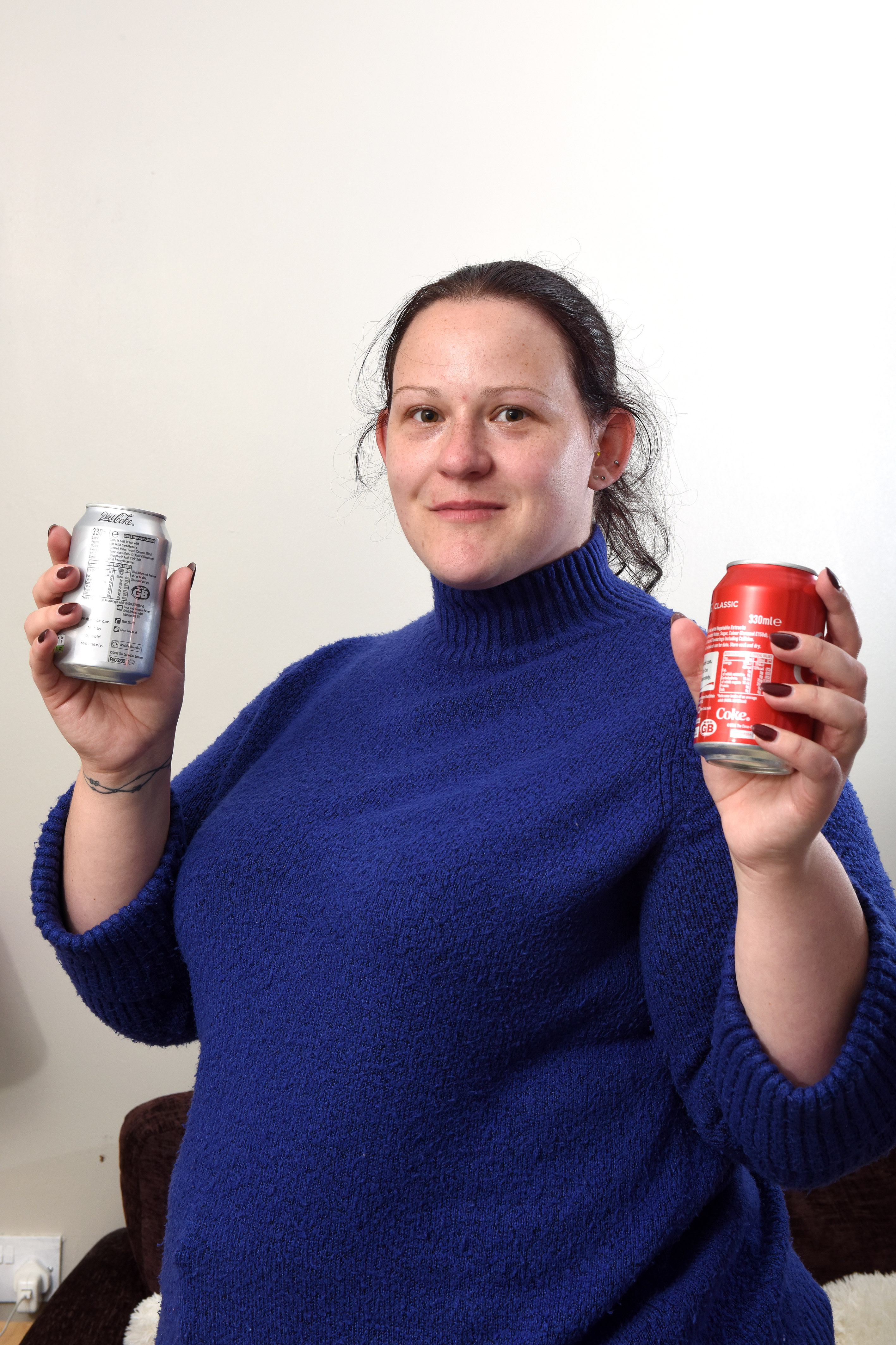 Elizabeth Perkins with two a can of diet cola which she is allergic to and a can of regular cola which she can have. [Photo: Caters]