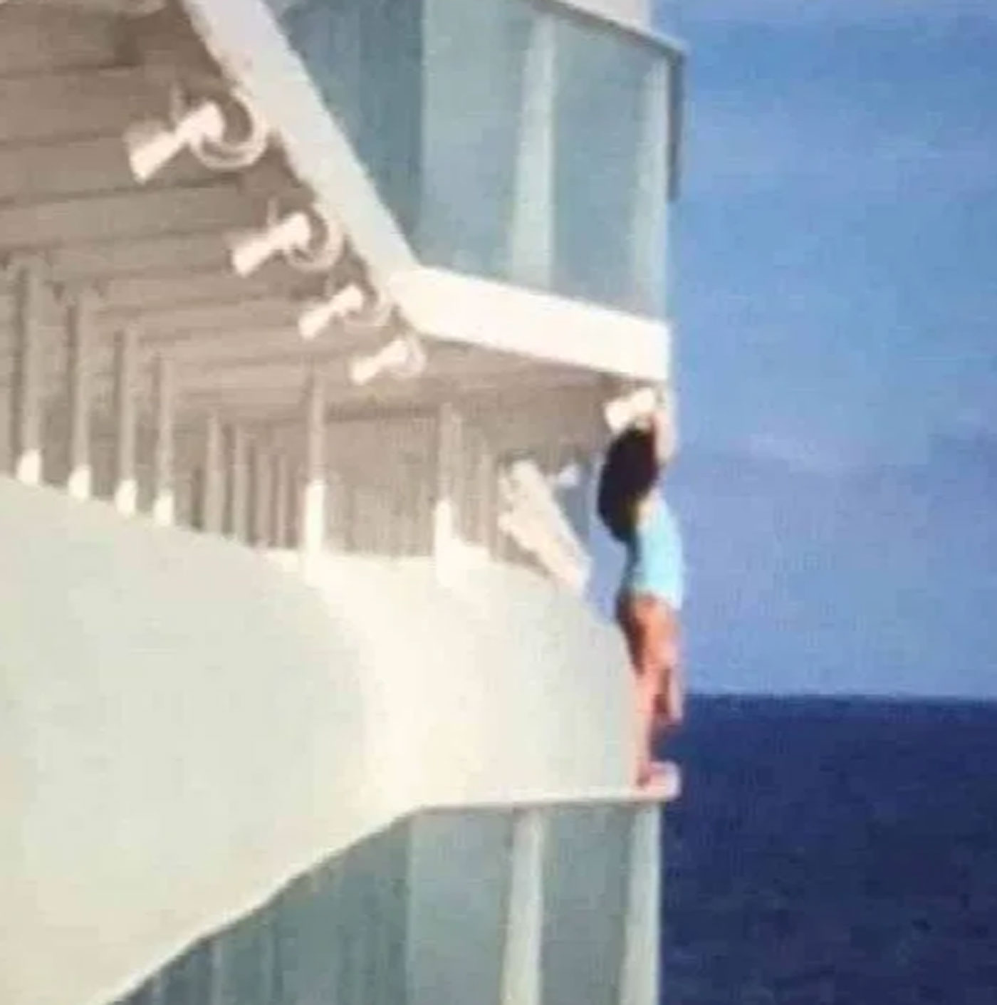 A passenger stands on the ledge of a Royal Caribbean Cruises ship.