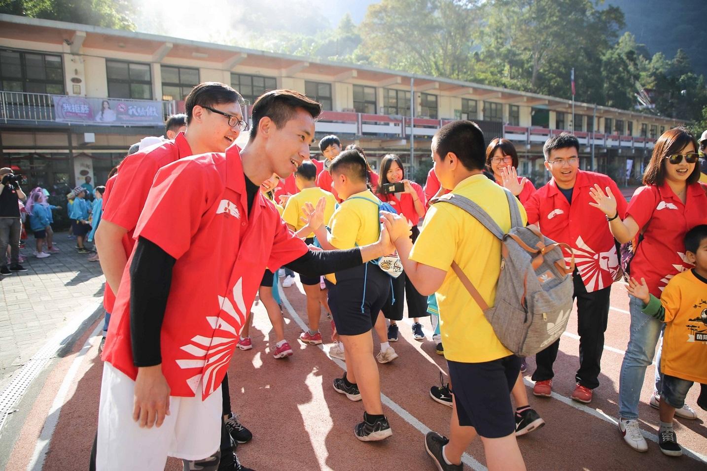 中華三菱志工列隊歡迎五峰國小小朋友參加跨校聯合運動。