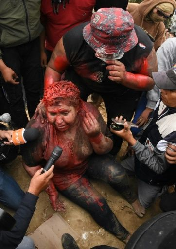 The mayor of the Bolivian town of Vinto, Patricia Arce, speaks to the press as she is being humiliated by a mob of opposition supporters who forcibly cut her hair and covered her in paint