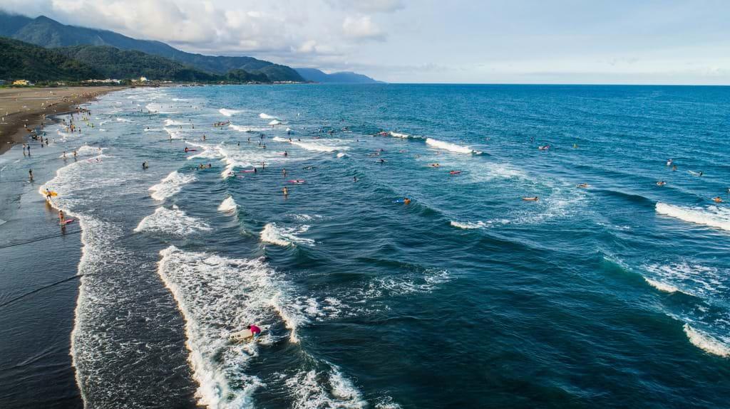 外澳沙灘緊鄰烏石港,戲水衝浪的遊客絡繹不絕。圖/宜蘭旅遊網