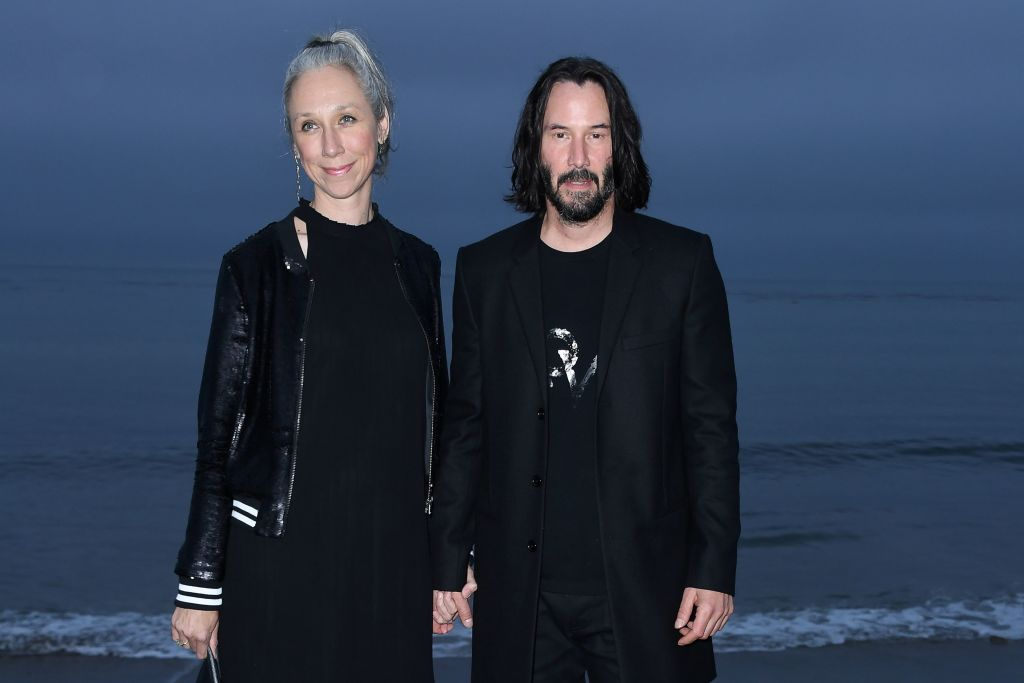 Alexandra Grant and Keanu Reeves arrive for the Saint Laurent runway show in Malibu, California, on June 6. (Photo: Valerie MACON/AFP via Getty Images)