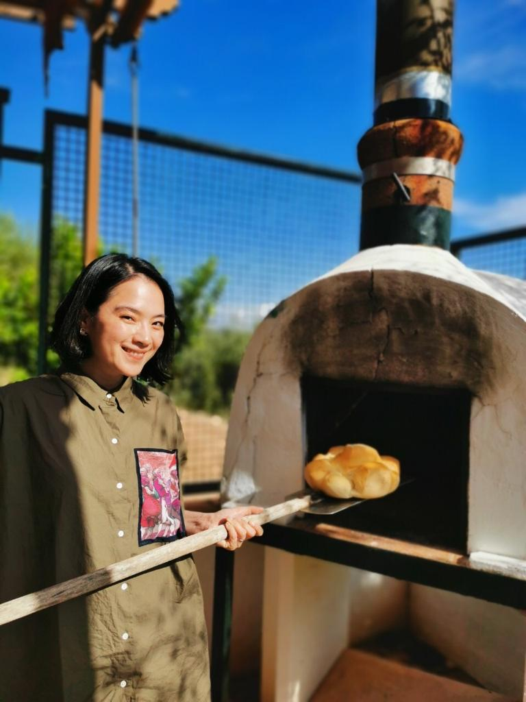 ▲午餐的麵包就從烤窯裡烤出來,讓她笑說:「我也拿一個假裝一下。」