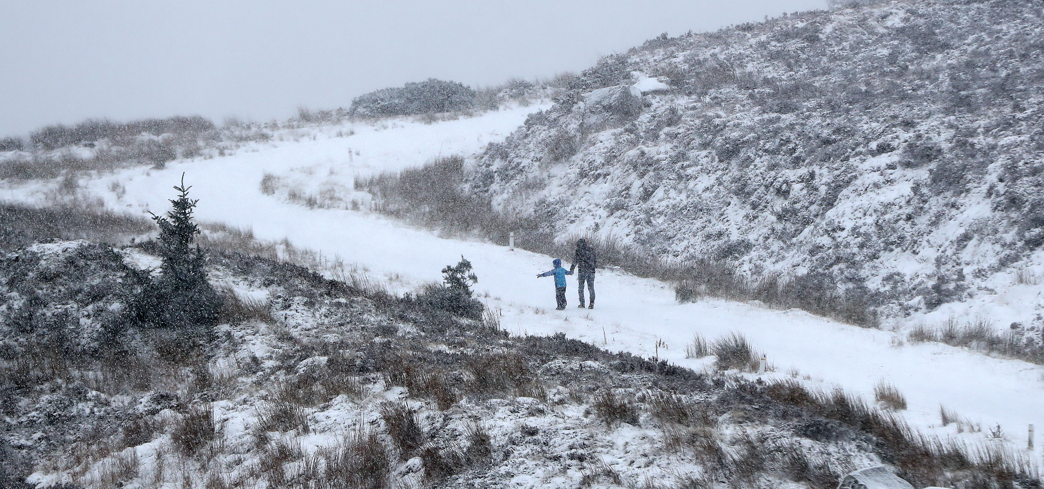 People walking in the snow in the Wicklow Gap, Co Wicklow. PA Photo. Picture date: Sunday December 15, 2019. See PA story WEATHER Rain . Photo credit should read: Niall Carson/PA Wire
