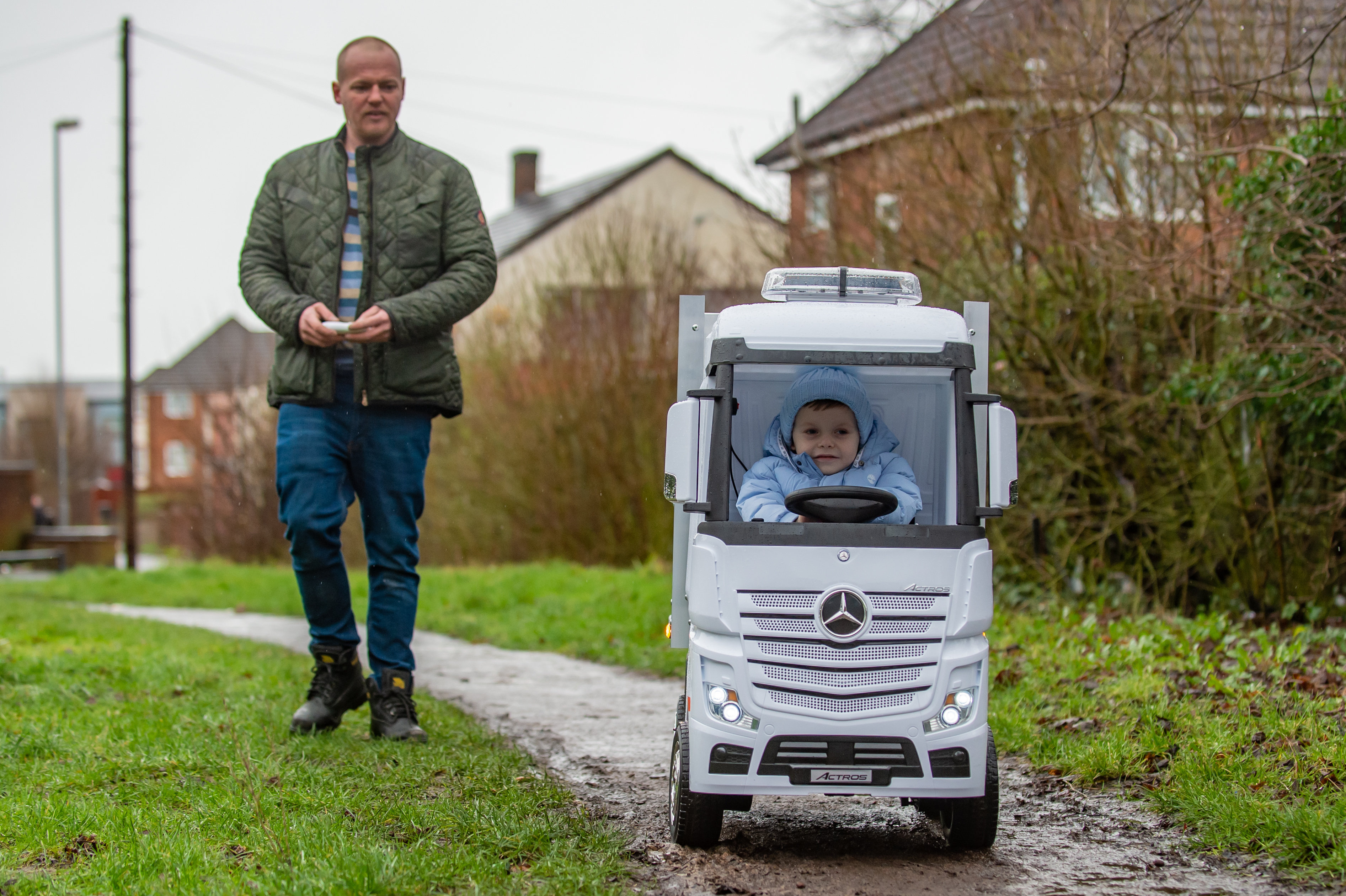 Darren Buckler with his nephew, Hugene Wilkes, 4, and the battery powered lorry he built for him. (SWNS)