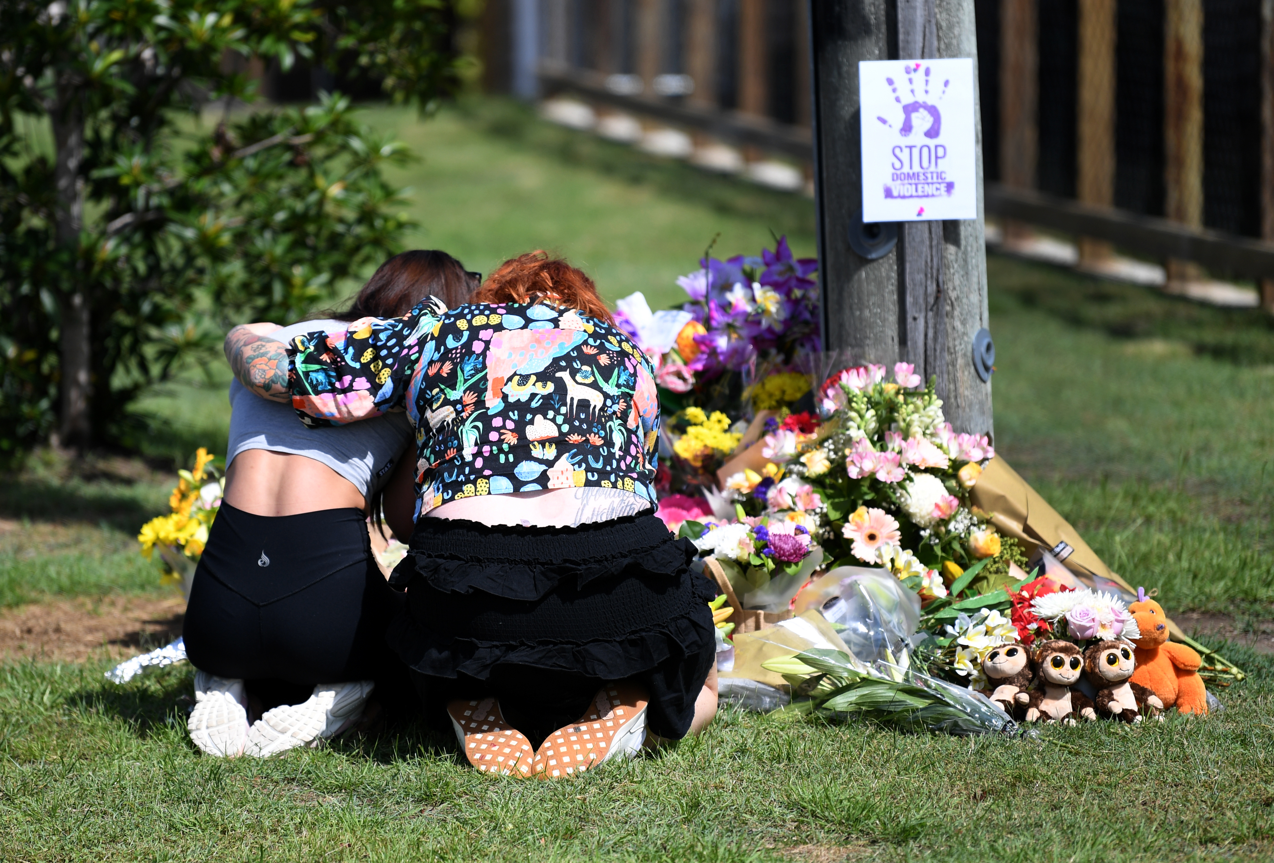 Mourners hug at the makeshift shrine near the scene of the tragedy at Camp Hill. Source: AAP