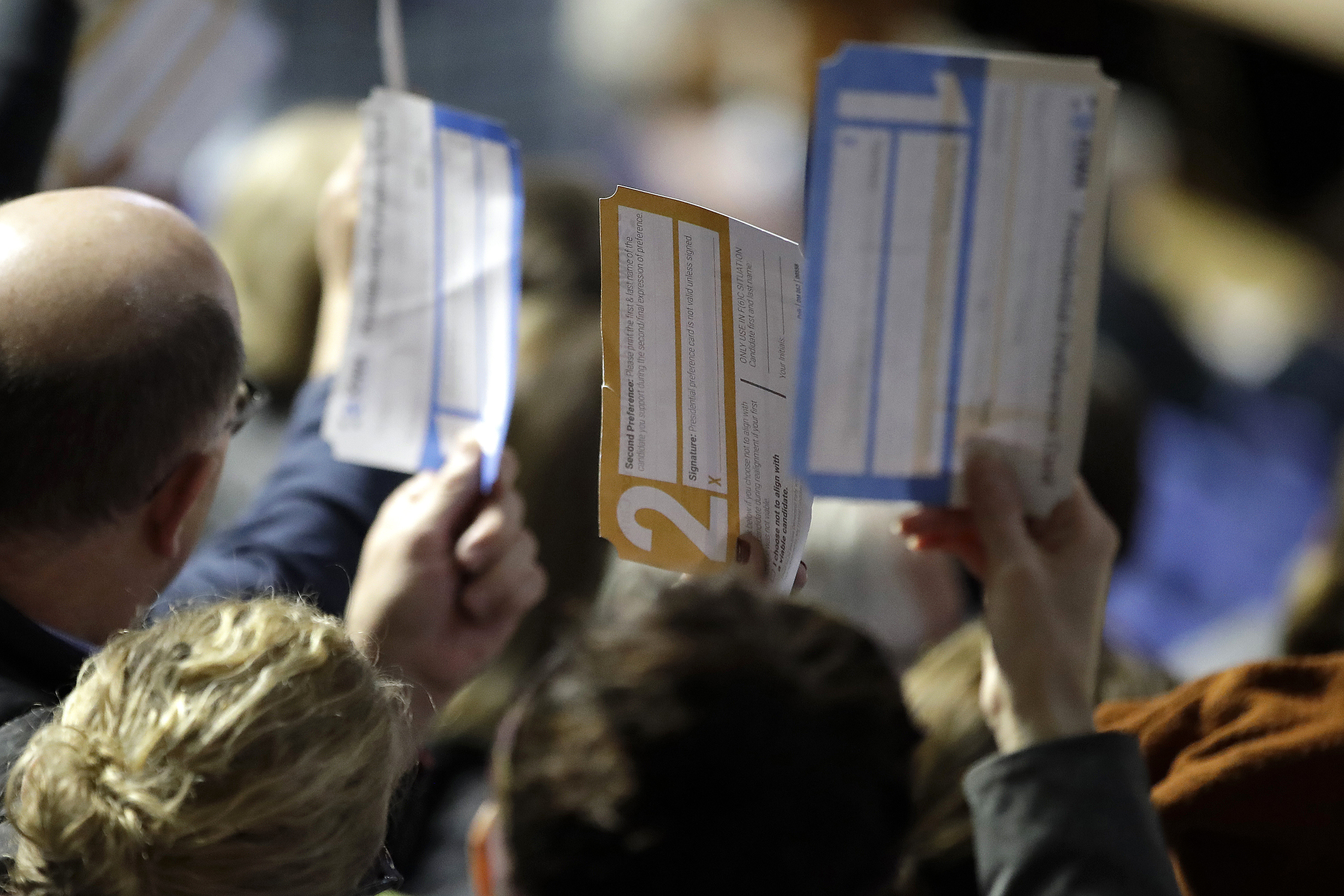 Precinct 68 Iowa Caucus voters seated in the Biden section hold up their first votes as they of the caucus as they are counted at the Knapp Center on the Drake University campus in Des Moines, Iowa, Monday, Feb. 3, 2020. (Gene J. Puskar/AP)