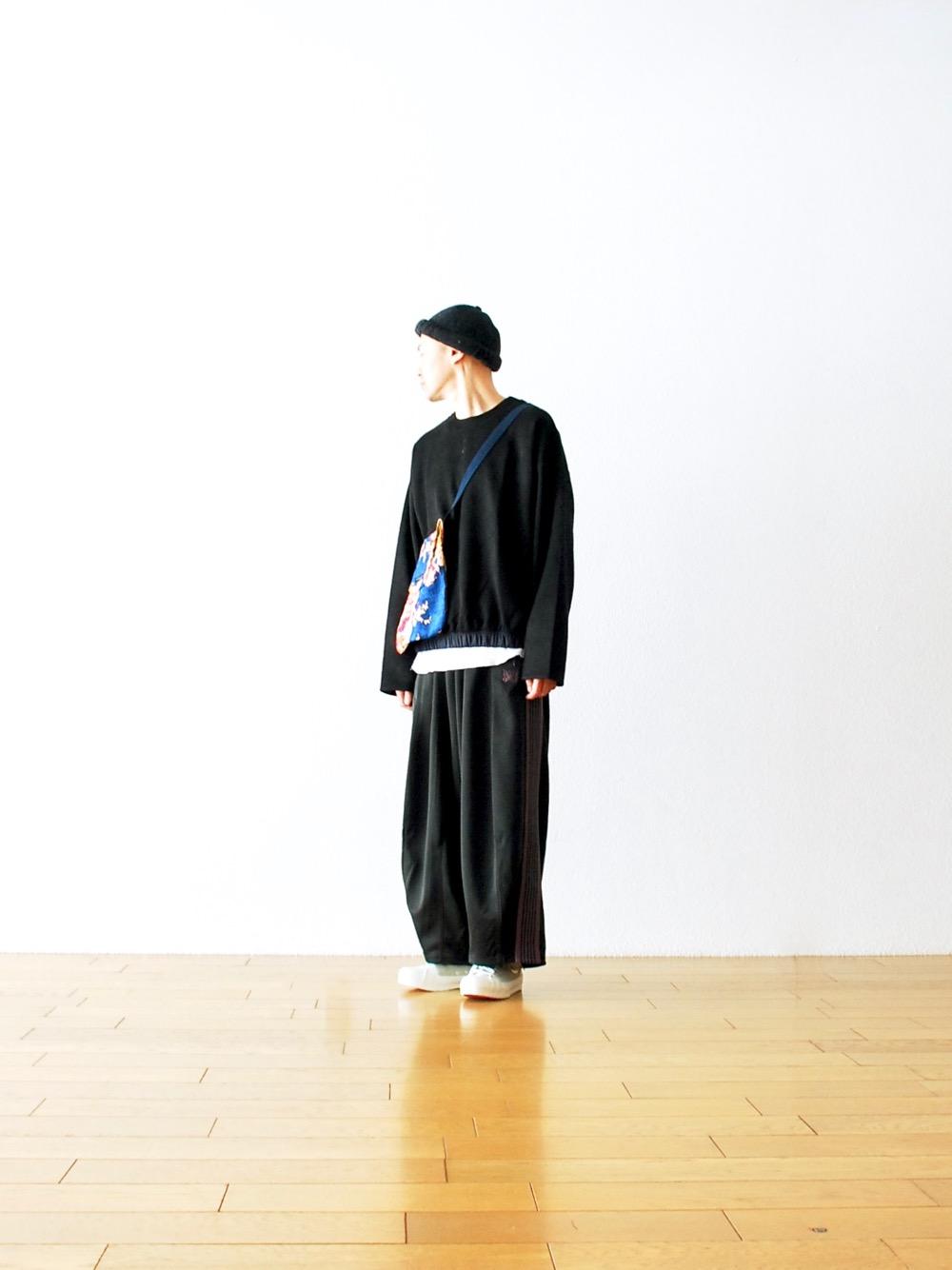有別於硬挺面料的運用,挑選人造材質製成、具有光澤感且輕薄的寬褲更能完美表現出獨有的垂墜感