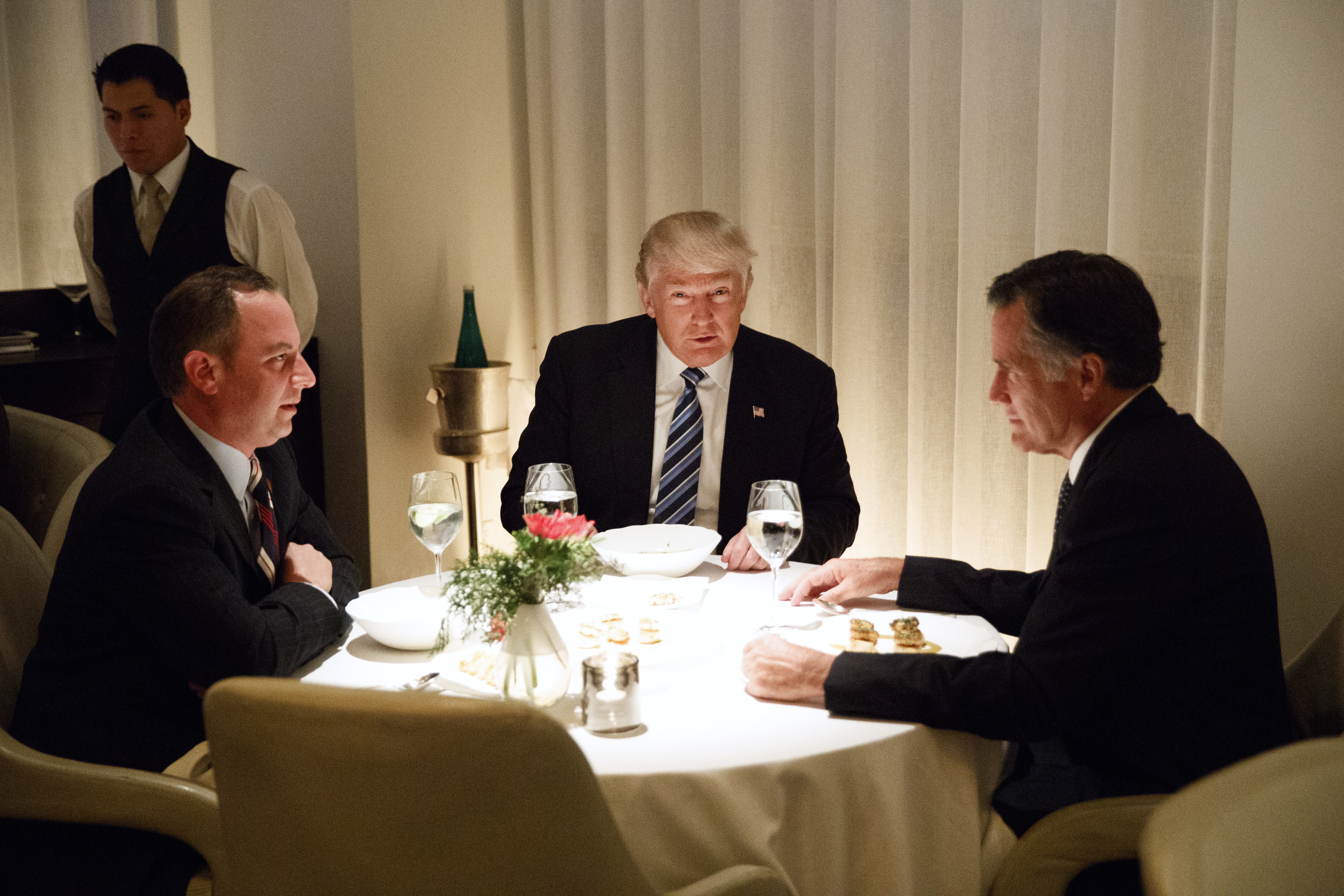 FILE - In this Nov. 29, 2016, file photo, shows President-elect Donald Trump, center, eating dinner with Mitt Romney, right, and Trump Chief of Staff Reince Priebus at Jean-Georges restaurant, in New York. Mitt Romney and President Donald Trump exchanged harsh criticisms of one another during the 2016 presidential campaign but also have a history of being willing to sit down with each other when mutually beneficial. Romney's announcement that he's running for the U.S. Senate seat in Utah creates the potential for future battles, or even deal-making.  (AP Photo/Evan Vucci, File)