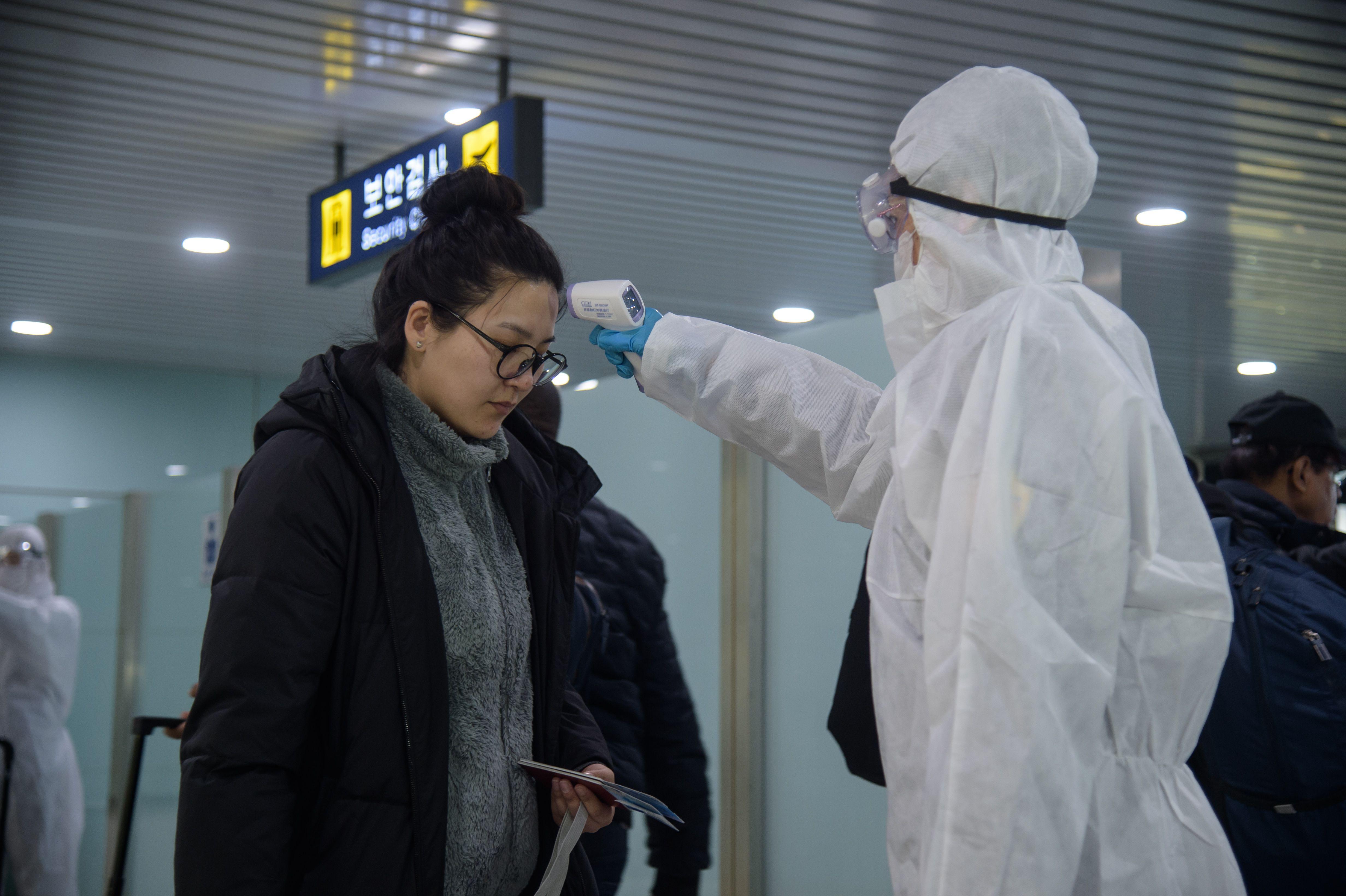 A woman has her temperature taken at Pyongyang International Airport.