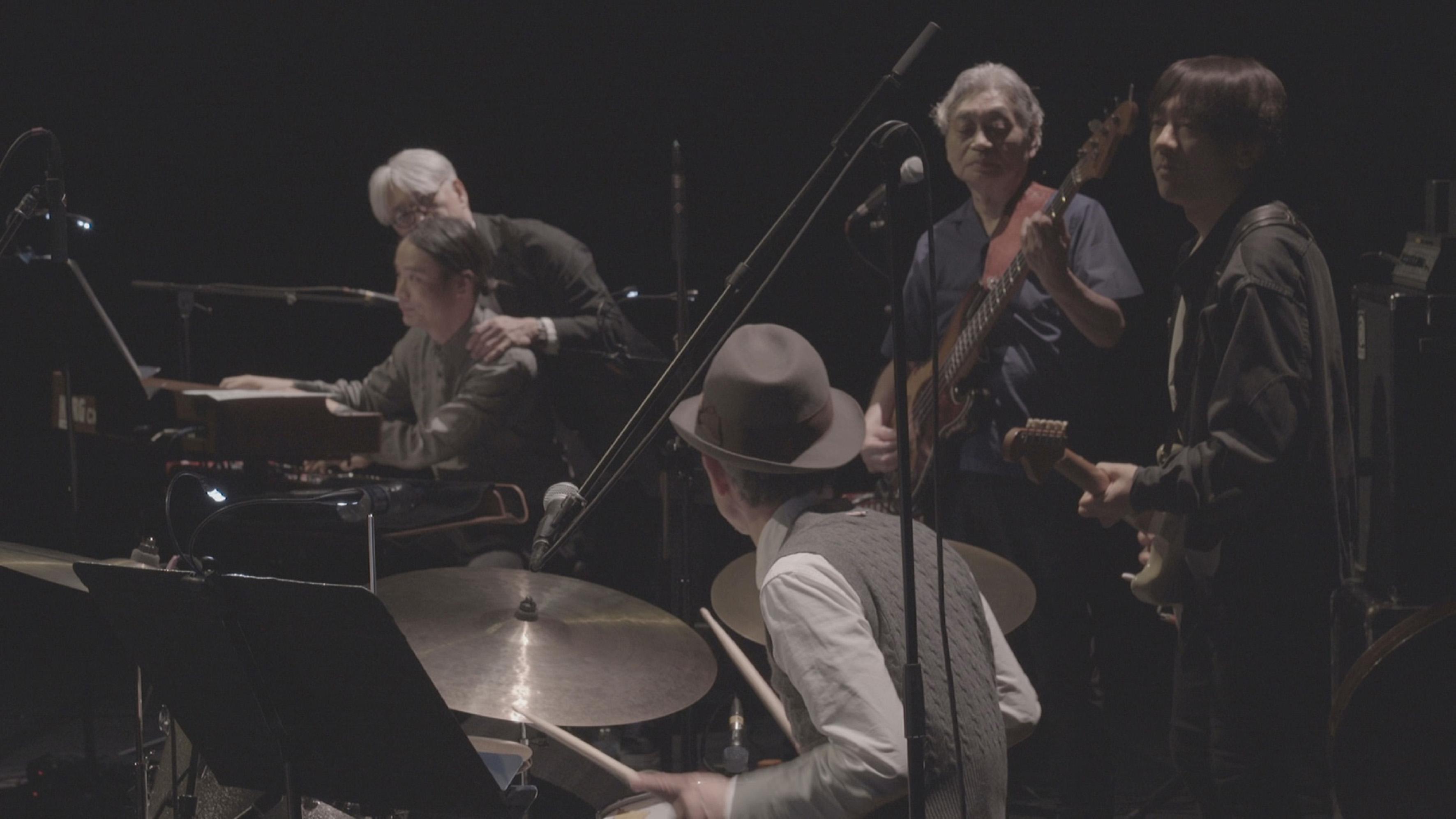 《搖滾師匠:細野晴臣》劇照_經典YMO於2018年英國演唱會上合體,坂本龍一(左,白髮)、細野晴臣(中,正面拿吉他的那位)、高橋幸宏(前,鼓手)