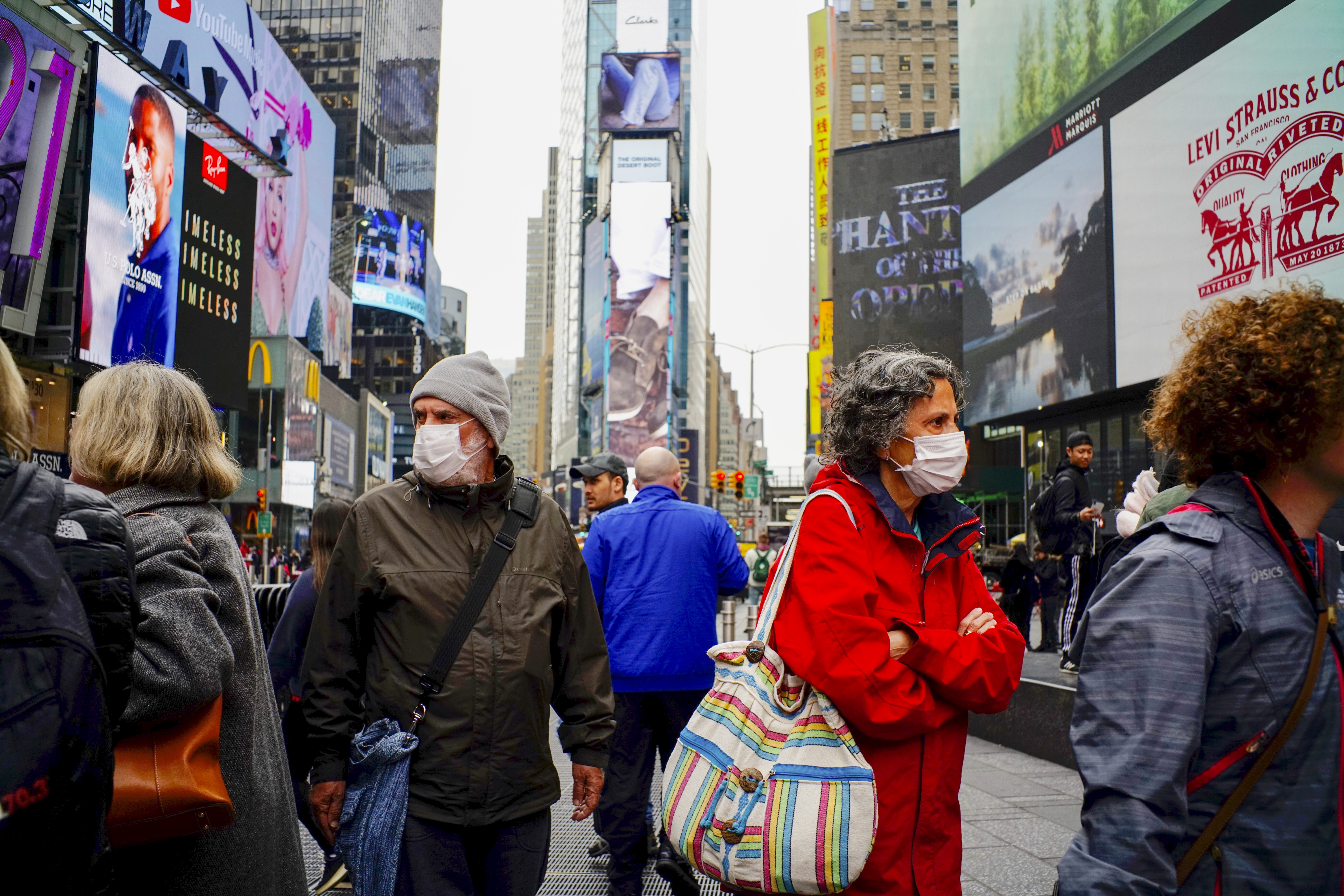 People wear face masks in Times Square New York on March 03, 2020. (Eduardo Munoz / VIEWpress via Getty Images)