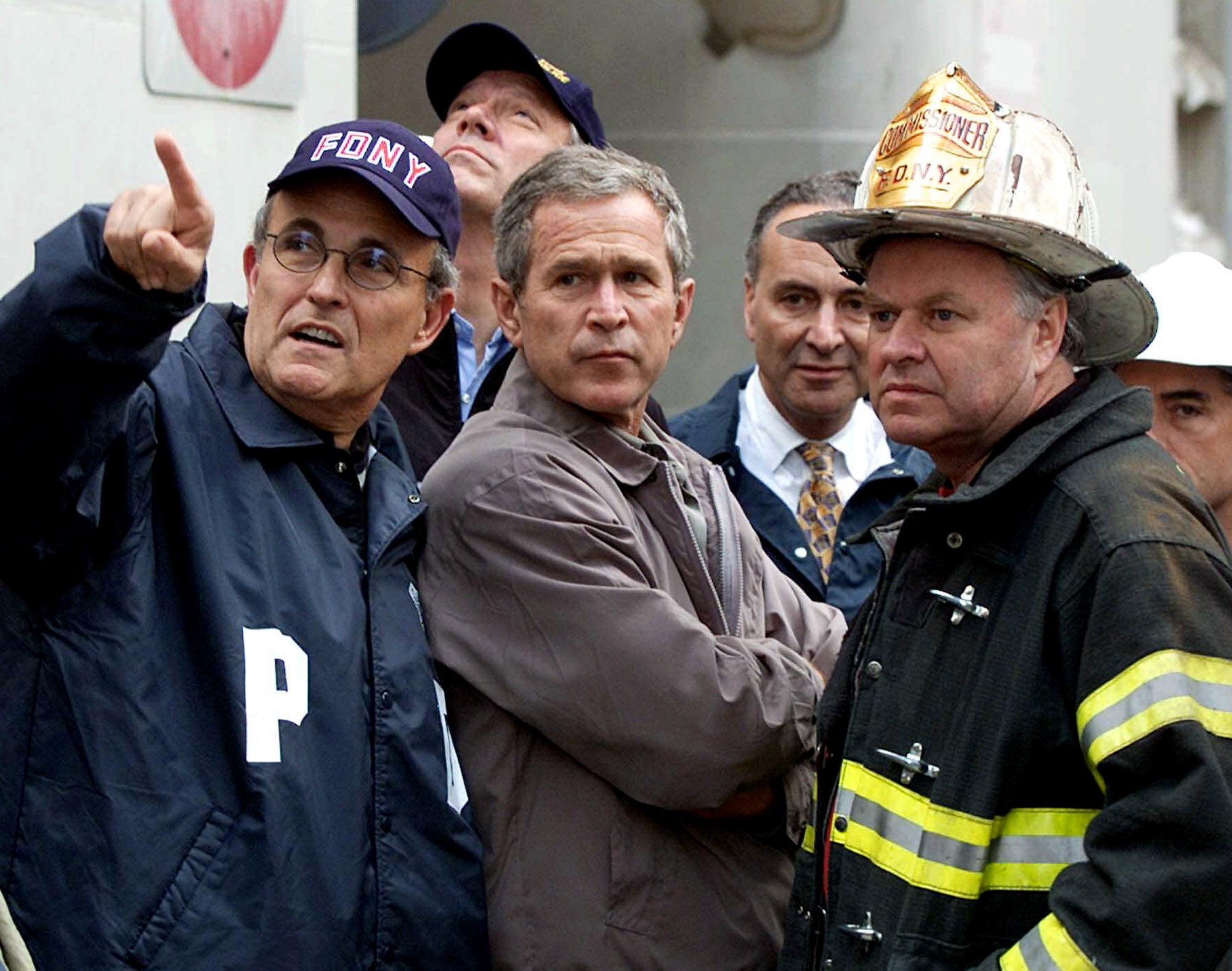President George W. Bush, center, with, from left, former New York City Mayor Rudolph Giuliani, then-New York Gov. George Pataki, Sen. Charles Schumer, D-N.Y., and former New York City Fire Commissioner Thomas Van Essen look toward the fallen buildings during a tour of the World Trade Center in New York on Sept. 14, 2001. (Doug Mills/AP)