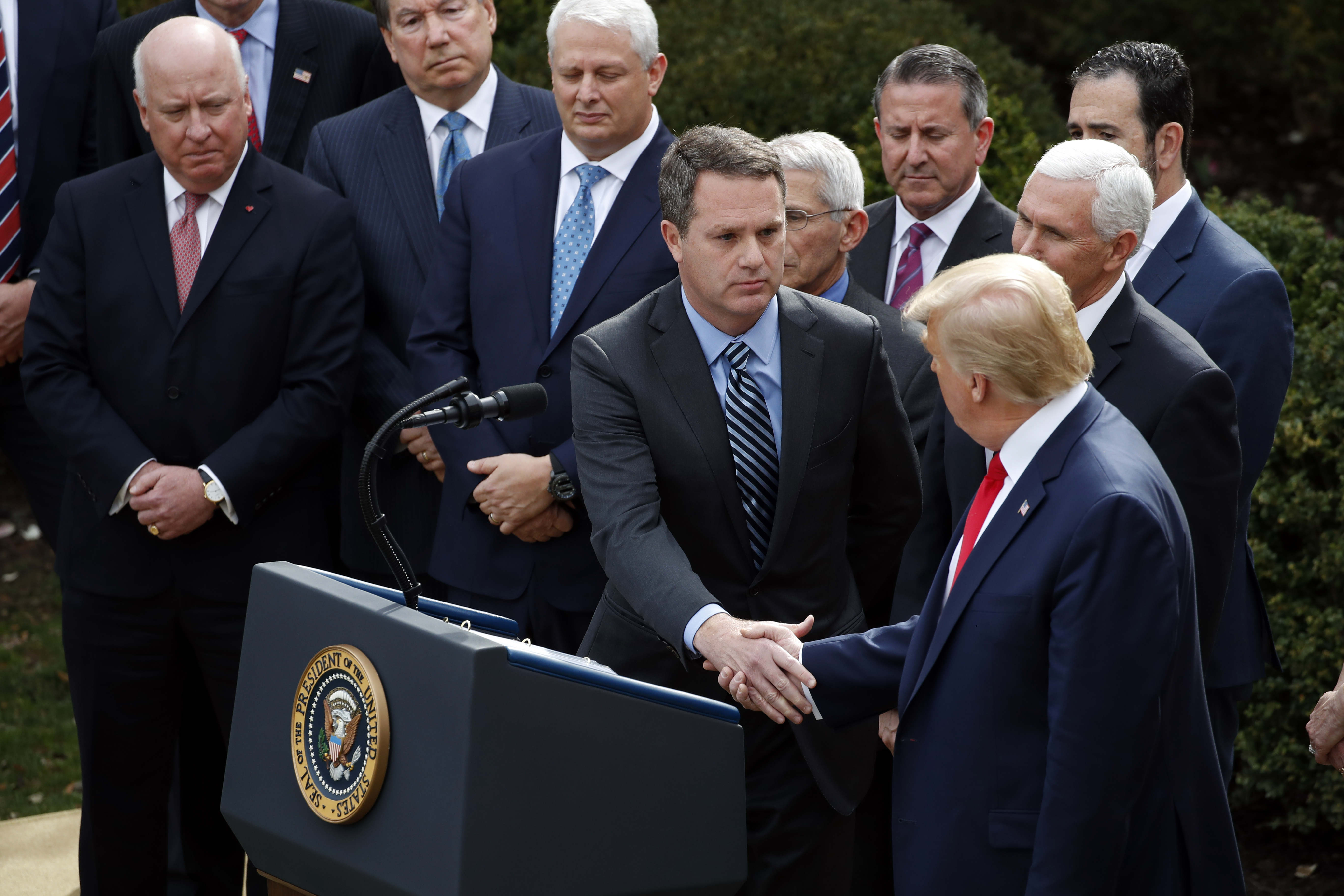 President Donald Trump shakes hands with Doug McMillon, president and CEO of Walmart Inc., during a news conference about the coronavirus in the Rose Garden at the White House on March 13, 2020, in Washington. (Alex Brandon/AP)