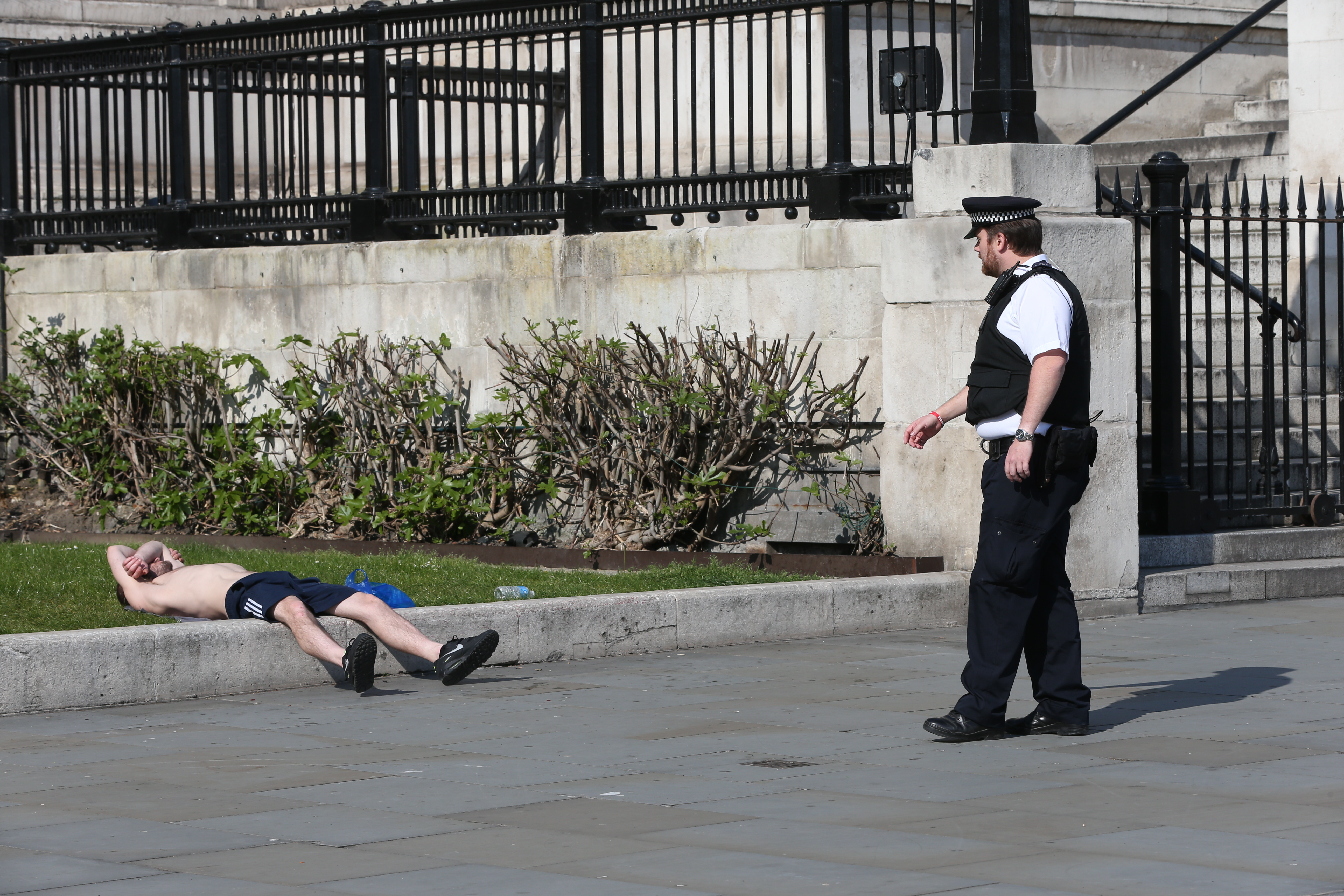 A Metropolitan police officer asks a sunbather to move along in front of the National Gallery in Trafalgar Square, London, as the UK continues in lockdown to help curb the spread of the coronavirus.