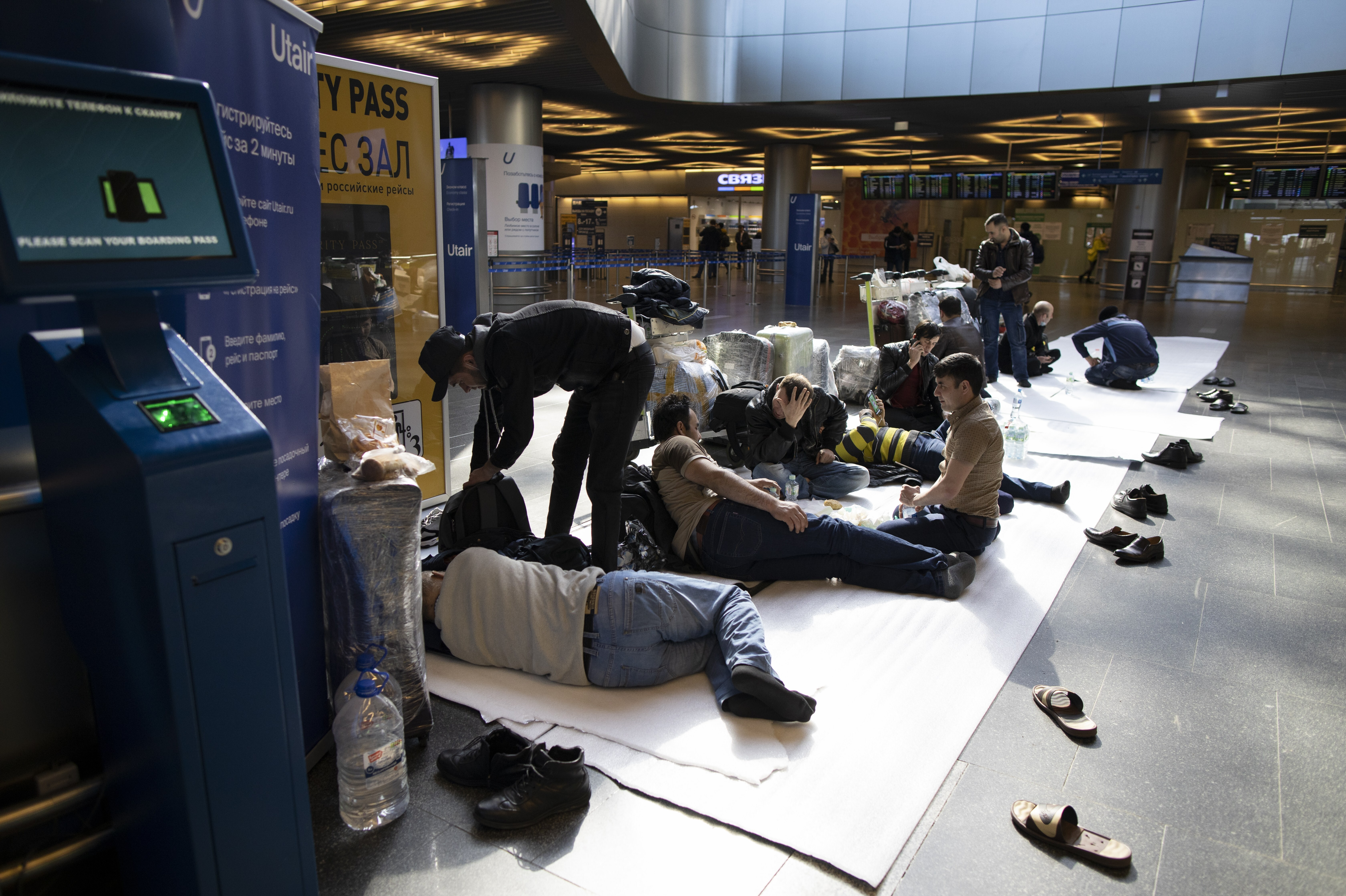 Tajikistan residents rest on the floor while waiting for a plane to their home country at the Vnukovo international airport in Russia amid the virus pandemic. Source: AAP